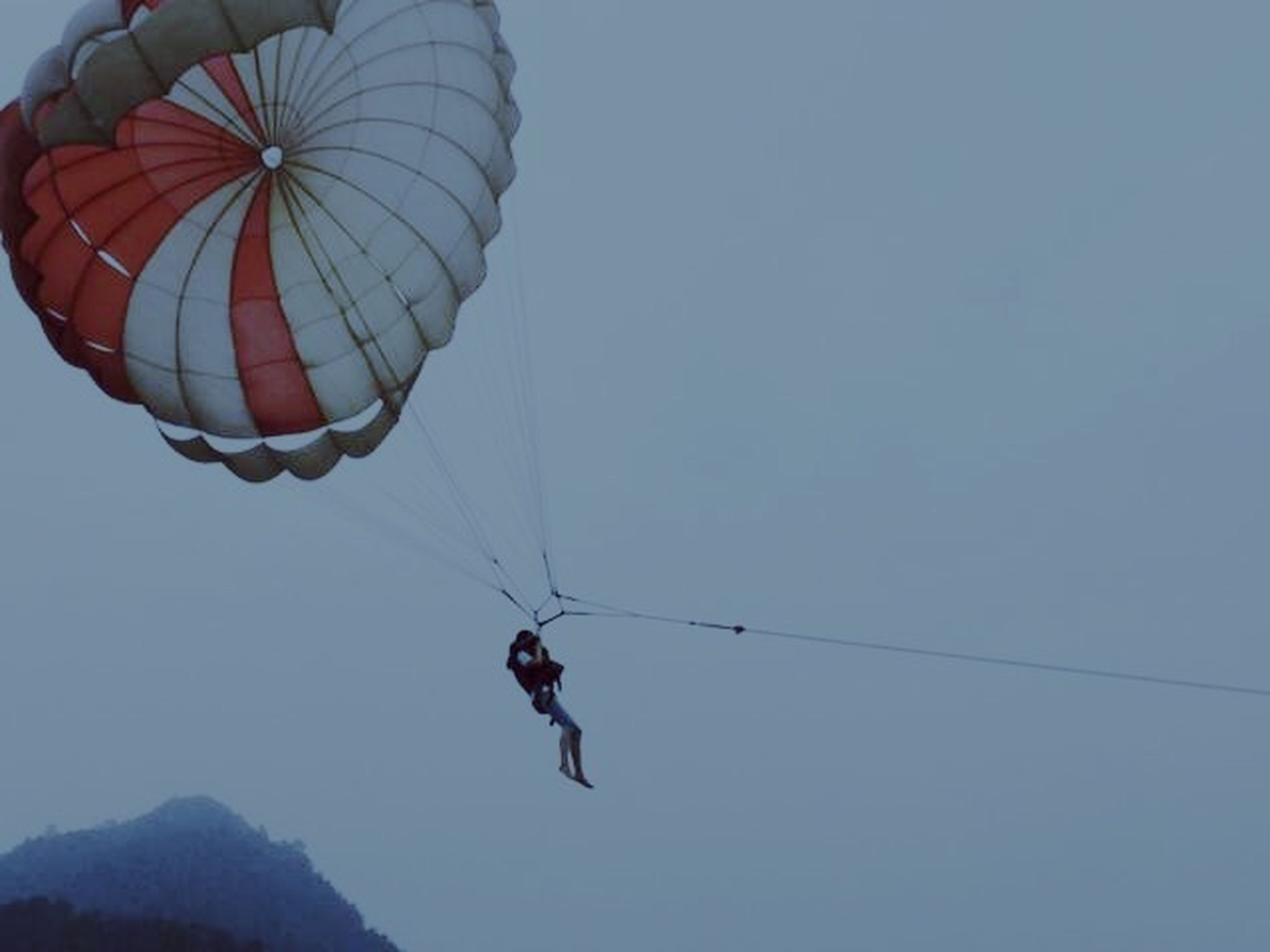 leisure activity, low angle view, mid-air, lifestyles, extreme sports, adventure, parachute, flying, men, clear sky, full length, paragliding, fun, sport, sky, exhilaration, copy space, freedom