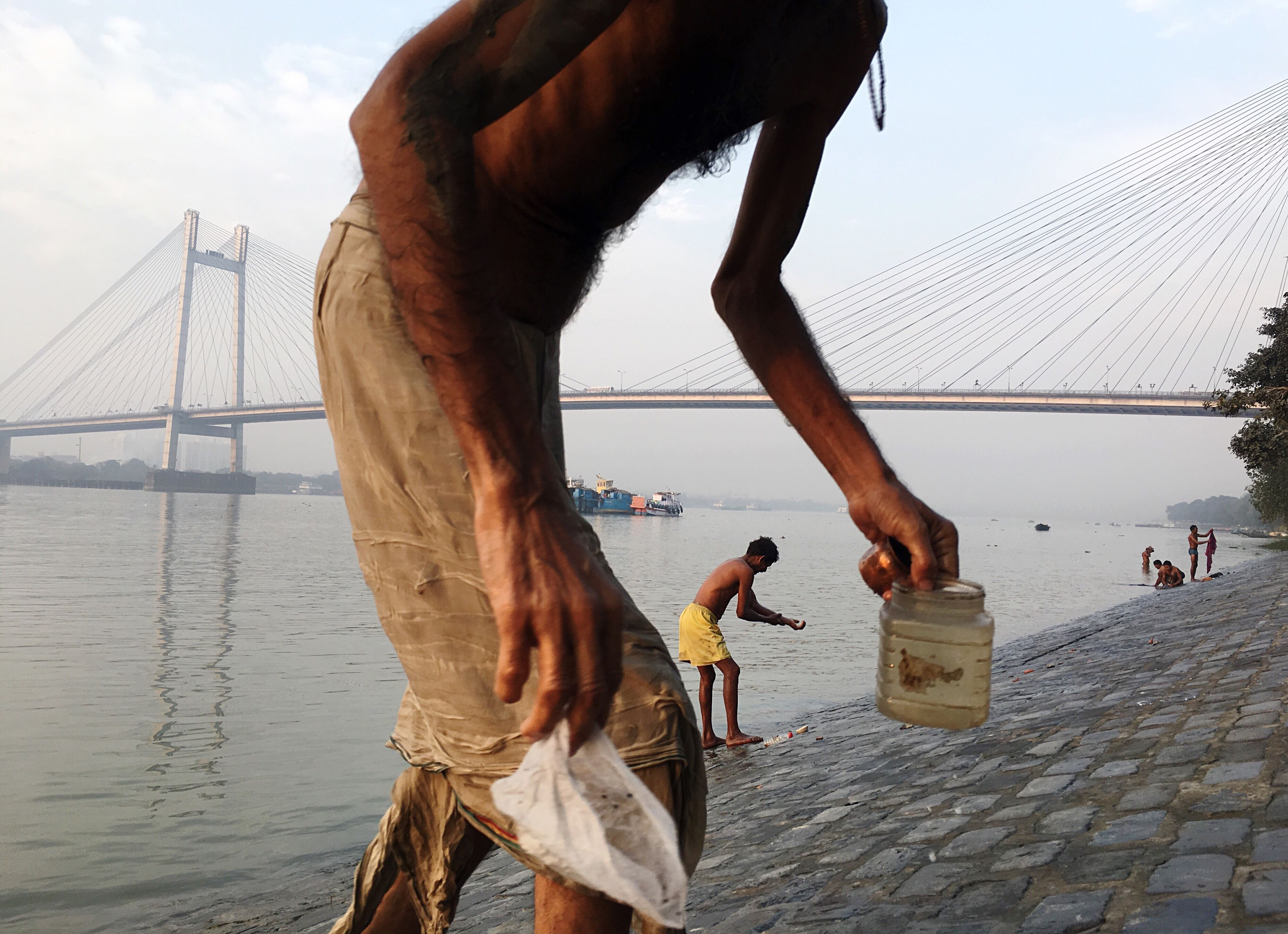 bridge - man made structure, water, real people, connection, architecture, sky, day, outdoors, built structure, men, suspension bridge, lifestyles, river, bridge, leisure activity, shirtless, women, one person, nature, city, mammal