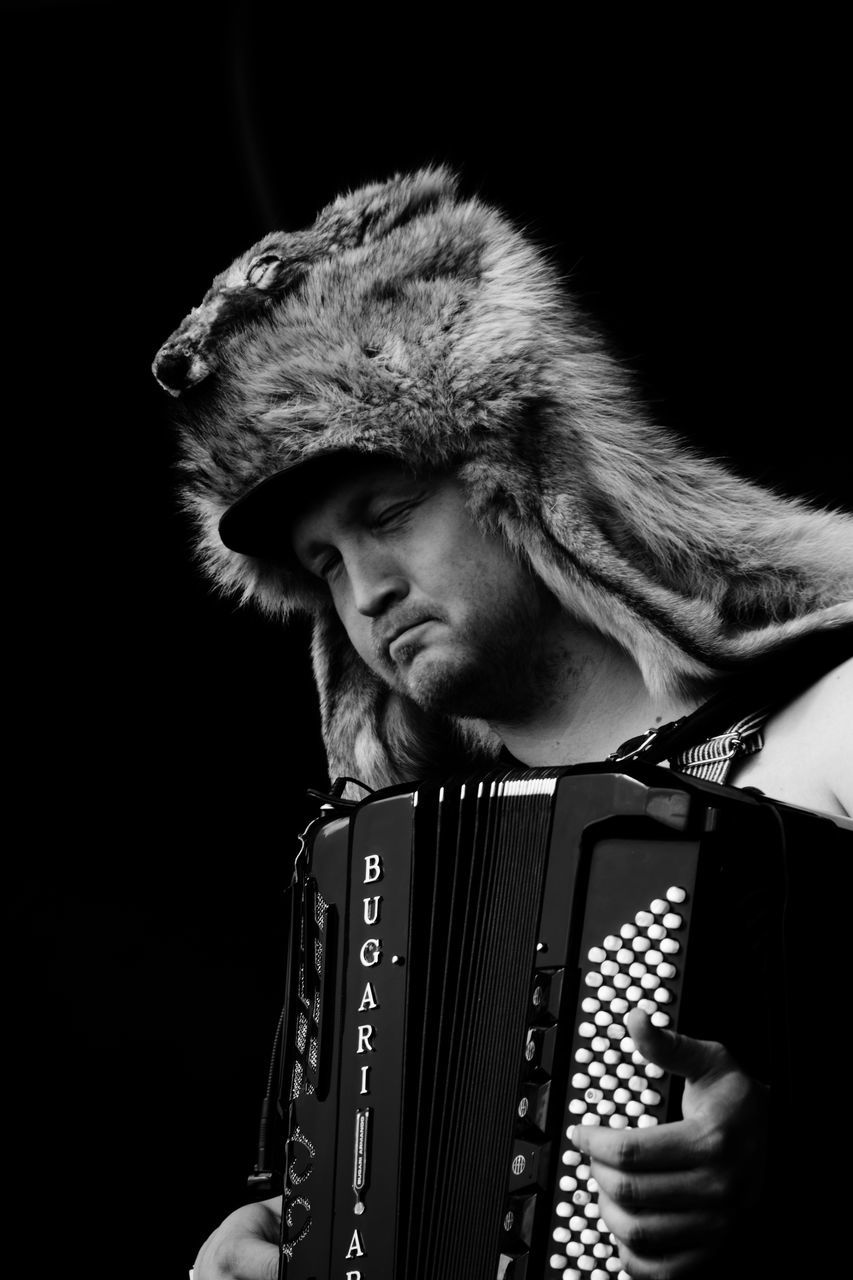 accordion, music, musical instrument, black background, real people, arts culture and entertainment, one person, playing, musician, studio shot, headshot, lifestyles, men, performance, one man only, outdoors, close-up, only men, day, adult, people