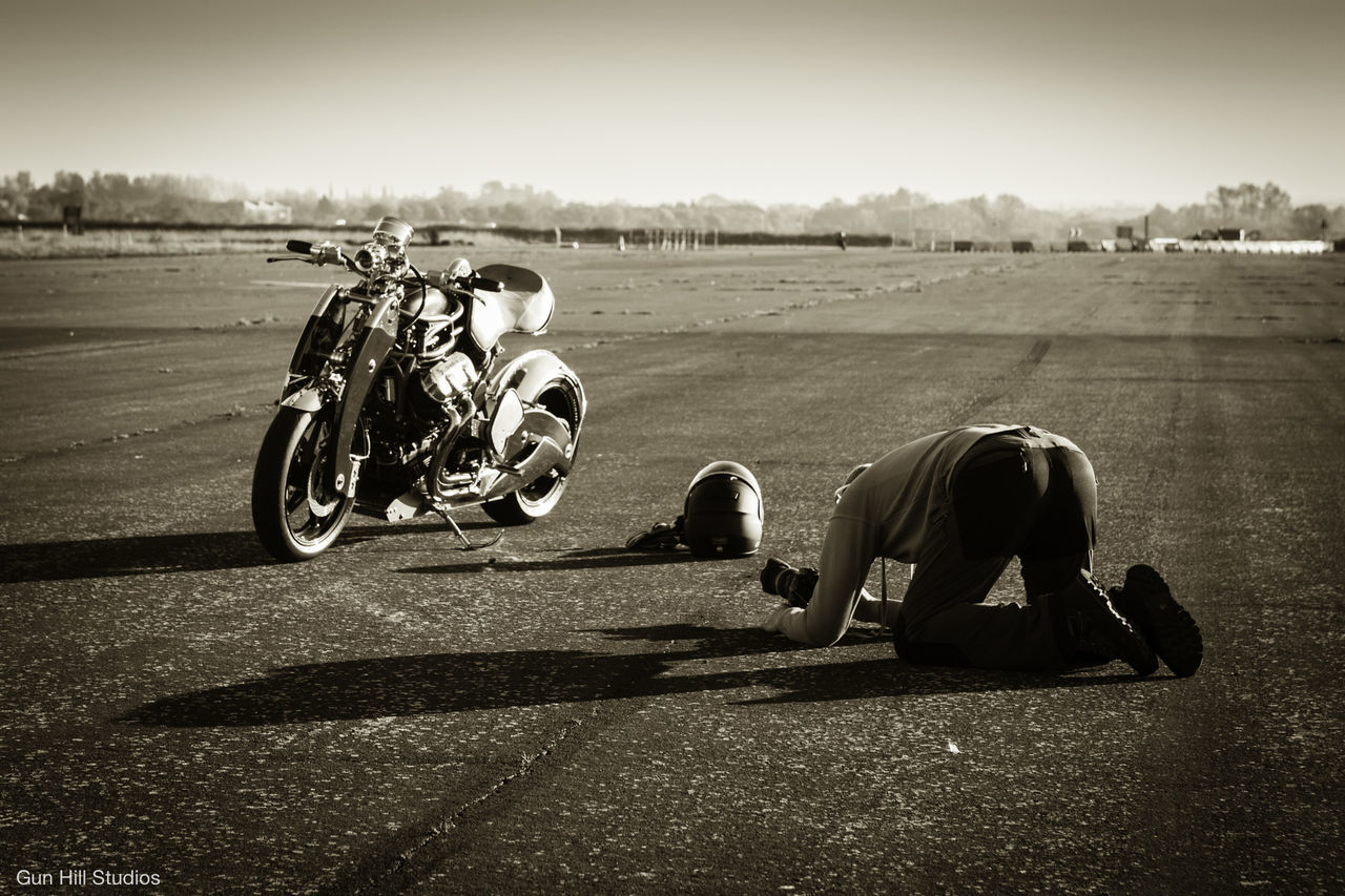 men, outdoors, full length, shadow, motorcycle, clear sky, real people, landscape, day, one person, one man only, sky, adult, people