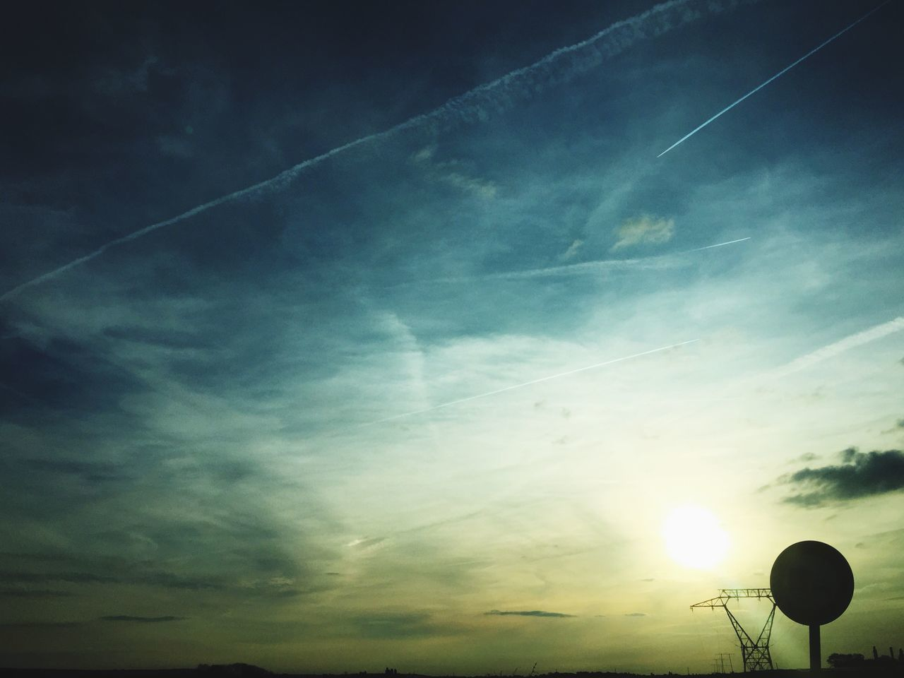 sunset, beauty in nature, low angle view, nature, sky, sunbeam, tranquility, tranquil scene, silhouette, sun, scenics, no people, outdoors, cloud - sky, contrail, vapor trail, day, astronomy