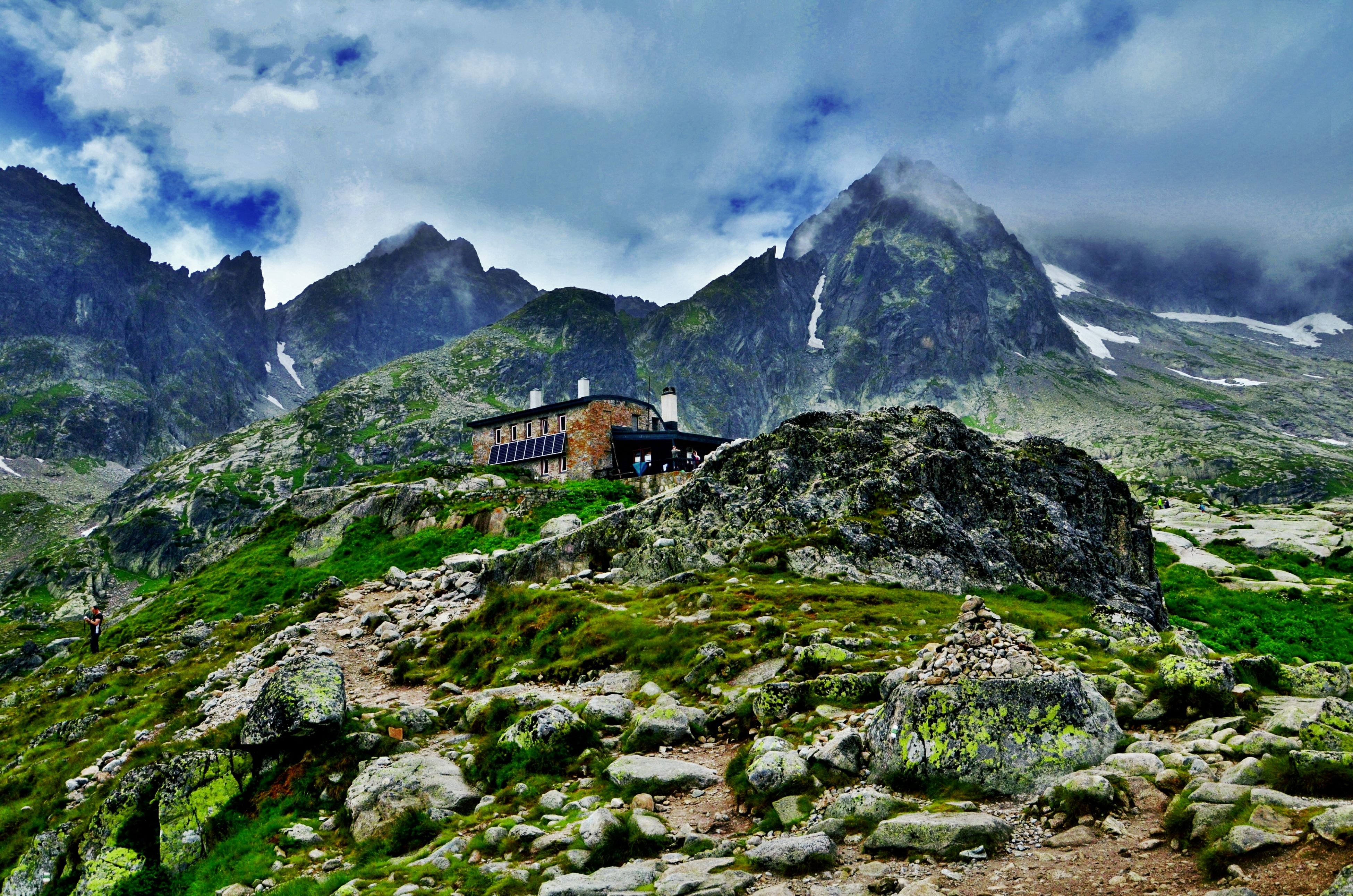 mountain, sky, architecture, built structure, mountain range, cloud - sky, building exterior, tranquil scene, tranquility, cloud, scenics, cloudy, landscape, nature, beauty in nature, house, rock - object, non-urban scene, day, green color