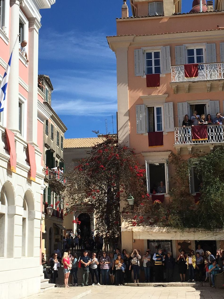 Crowds in St Spiridon Square, Corfu Town, wait for the Greek Orthodox Easter tradition of throwing red clay pots from the tops of buildings smashing into the street below Architecture Building Building Exterior Built Structure Celebrations City City Life Cloud Corfu Town Crowd Day Façade Greek Easter Large Group Of People Lifestyles Outdoors Religious Traditions Residential Building Residential Structure Sky St Spiridon Square Original Experiences