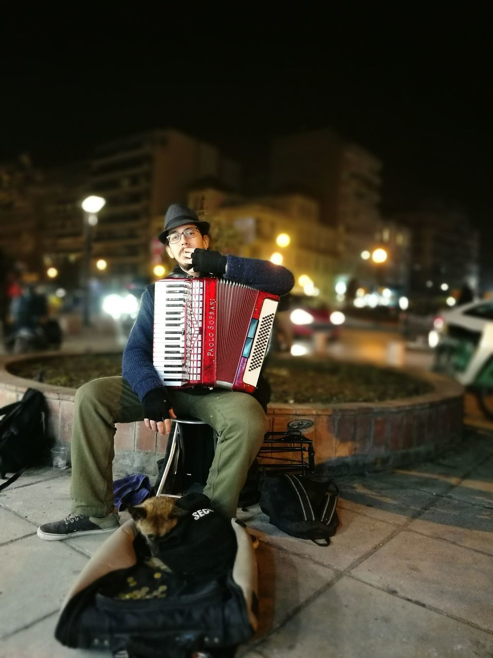 accordion, night, real people, illuminated, musical instrument, music, young adult, one person, arts culture and entertainment, lifestyles, full length, young men, outdoors, musician, leisure activity, men, city, young women, people