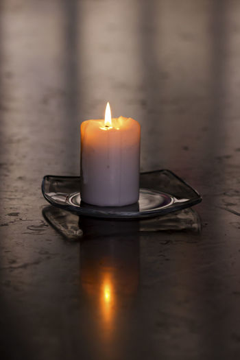 A single burning candle on a glass plate on top of a big polished stone table in a church Copy Space Hope Peace Solemn Spirituality Tranquility Burning Candle Candlelight Close-up Concept Flame Glowing Illuminated Indoors  Mourn No People Reflection Religion Sadness Single Object Stone Material Symbol Table White Color