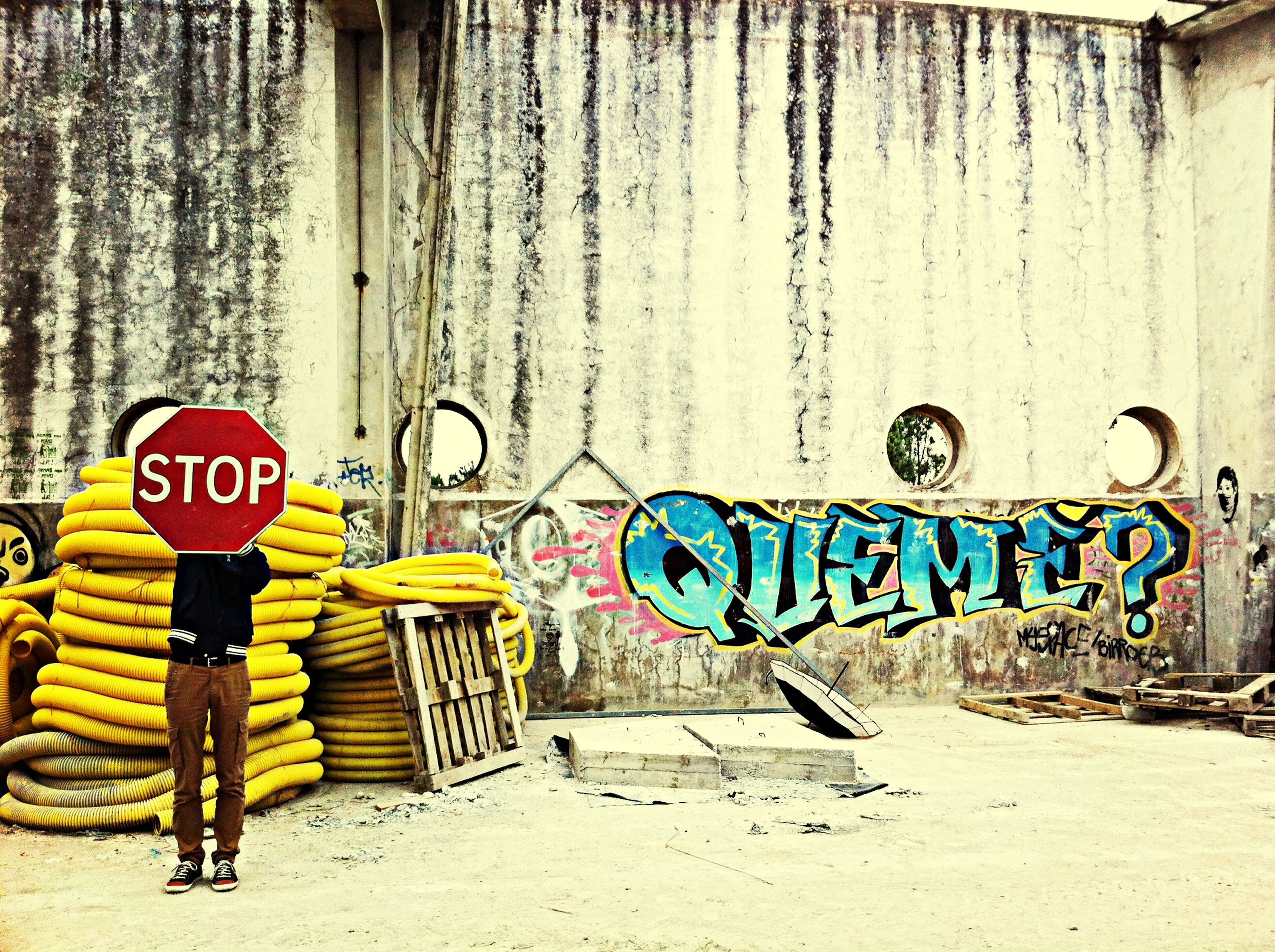 graffiti, text, wall - building feature, western script, communication, built structure, wall, architecture, day, street, men, walking, outdoors, lifestyles, full length, rear view, street art, sign