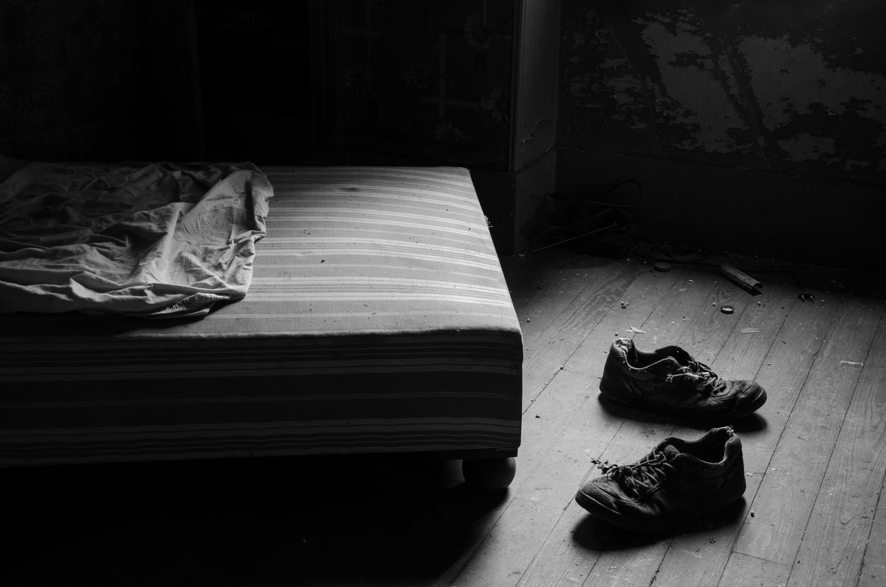 Empty Shoes Near Bed At Home