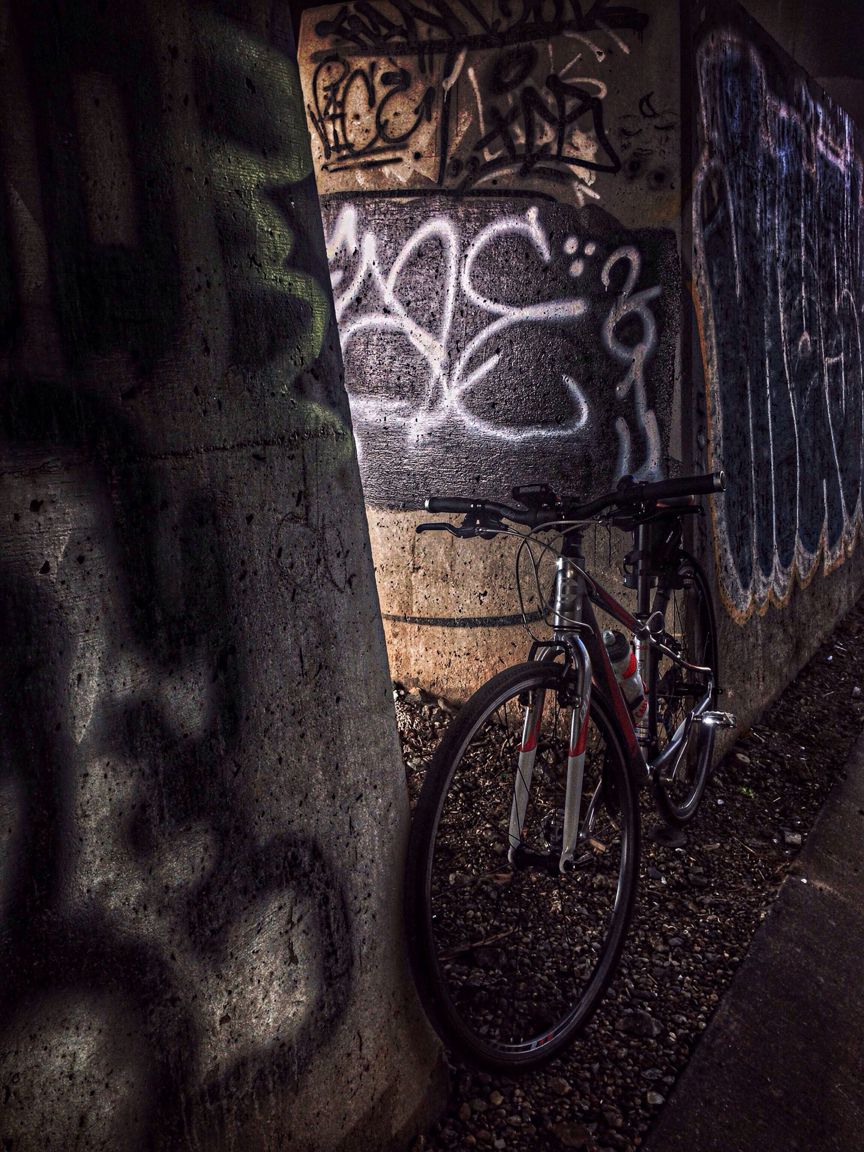 wall - building feature, bicycle, indoors, wall, graffiti, shadow, no people, built structure, sunlight, old, architecture, art, absence, high angle view, day, art and craft, close-up, sidewalk, stationary, parking