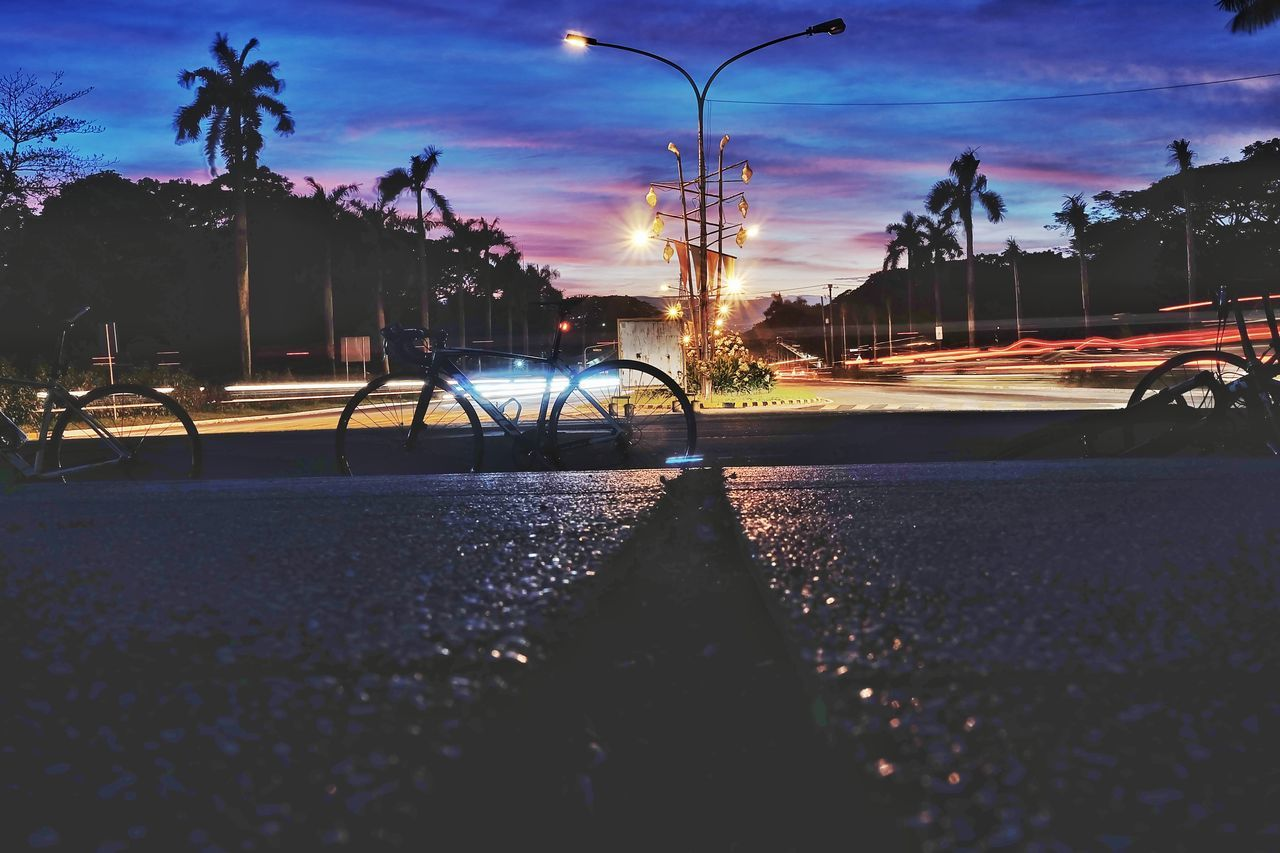street, transportation, street light, outdoors, sky, road, car, sunset, tree, city, illuminated, night, no people, building exterior, palm tree, architecture, nature