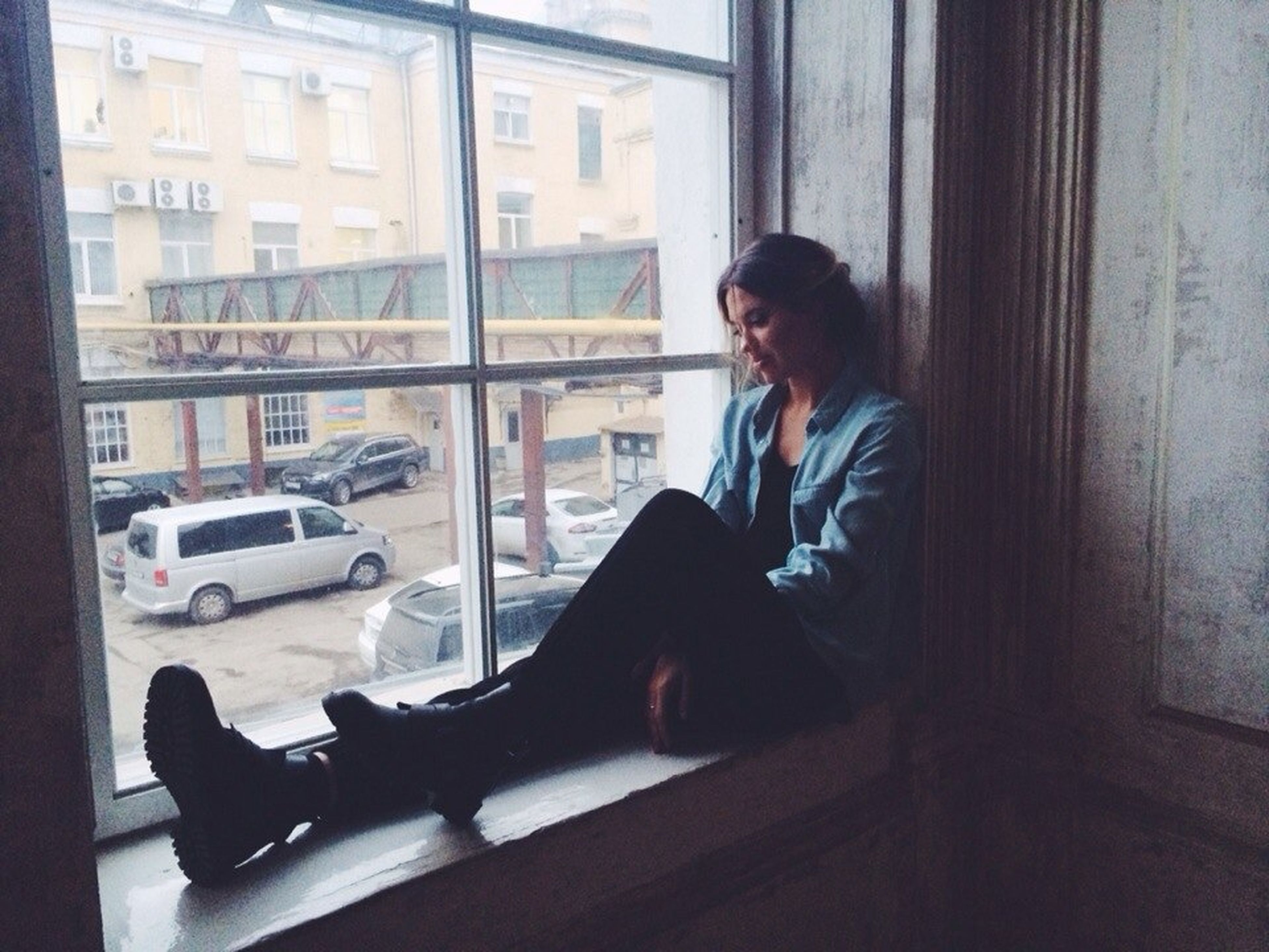 sitting, indoors, young adult, window, full length, lifestyles, side view, leisure activity, architecture, person, glass - material, built structure, three quarter length, casual clothing, young women, waist up, standing, looking away