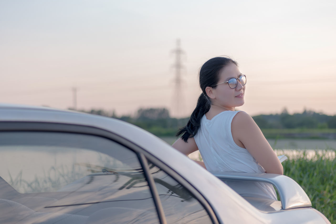 Car Casual Clothing Day Focus On Foreground Land Vehicle Leisure Activity Lifestyles Medium-length Hair Mode Of Transport Nature One Person Outdoors Real People Sky Standing Sunglasses Sunset Transportation Tree Young Adult Young Women