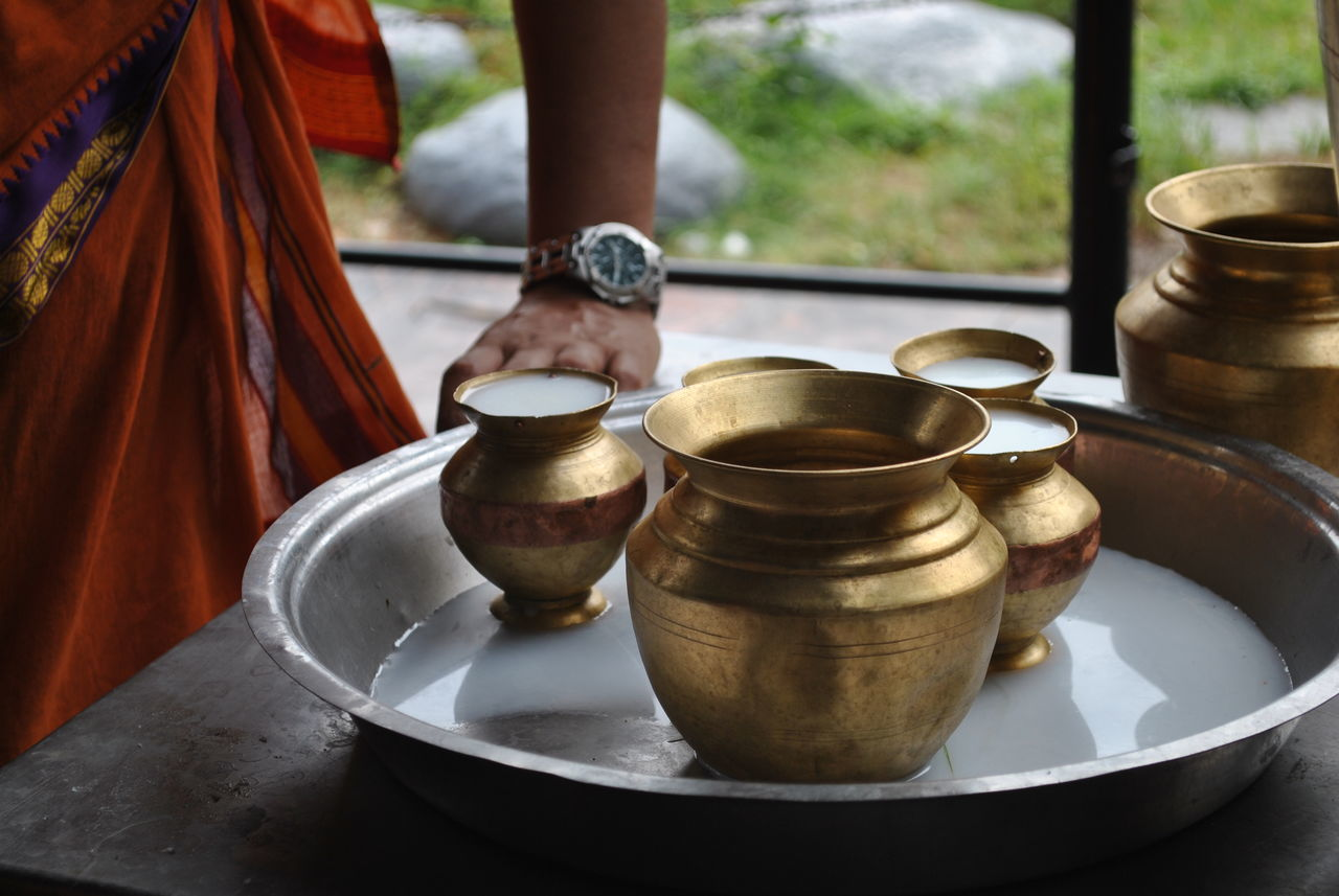 Midsection Of Man Standing By Milk In Utensils On Table At Buddhist Temple