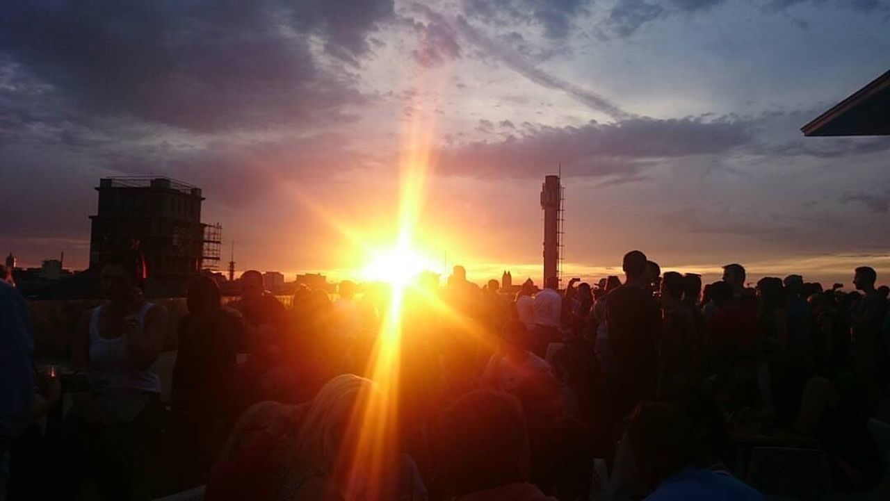 Sunset Sun Large Group Of People Sunbeam Person Orange Color Sky Bright Outdoors Beauty In Nature Lens Flare Nature Tranquil Scene City Life Scenics Cloud - Sky Crowd Rooftop Atmosphere Building Story