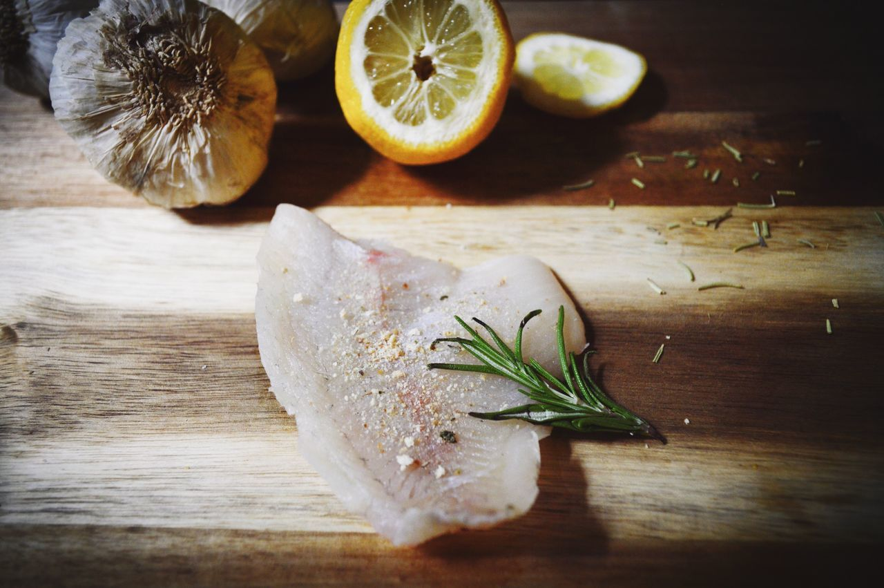 Raw bluegill fillet seasoned with a pinch of garlic and lemon pepper, garnished with rosemary on wooden surface Freshness Table Fruit Healthy Eating SLICE Rosemary Food And Drink Food No People Close-up Cross Section Fish Fillet Raw Fish Fish Rustic Food Rustic Food Flat Lays Fish Fillet Raw Meat   Meat Flatlay Flat Lay Wood Surface Fish On Wood