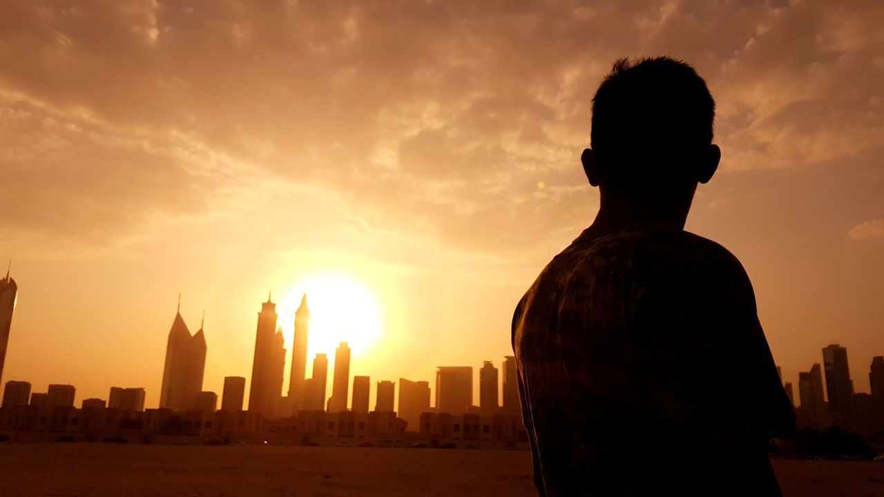 sunset, sky, architecture, skyscraper, built structure, building exterior, city, cityscape, real people, cloud - sky, urban skyline, travel destinations, rear view, outdoors, silhouette, men, one person, leisure activity, modern, nature, day, people
