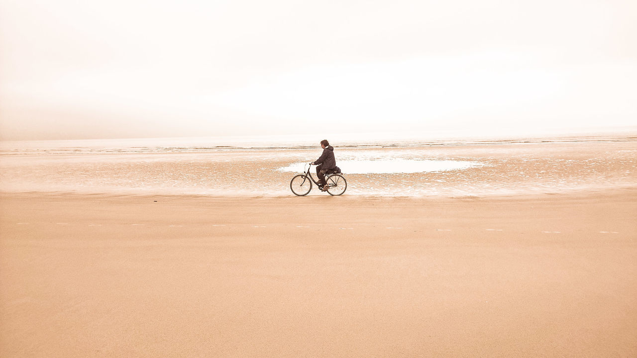 beach, sea, sand, nature, shore, riding, tranquil scene, scenics, one person, outdoors, beauty in nature, real people, water, sky, full length, tranquility, horizon over water, lifestyles, clear sky, day, arid climate, people