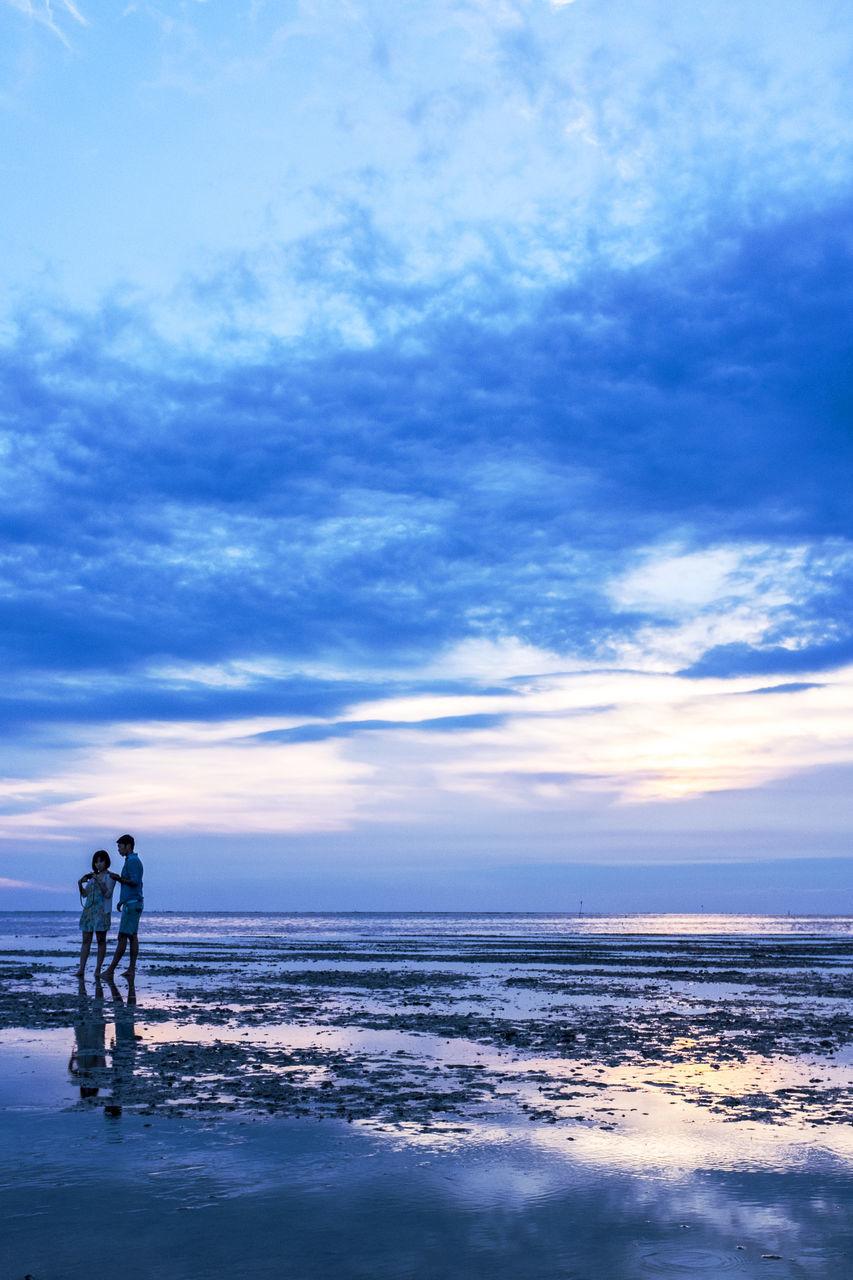 Couple Standing On Beach Against Cloudy Sky At Dusk