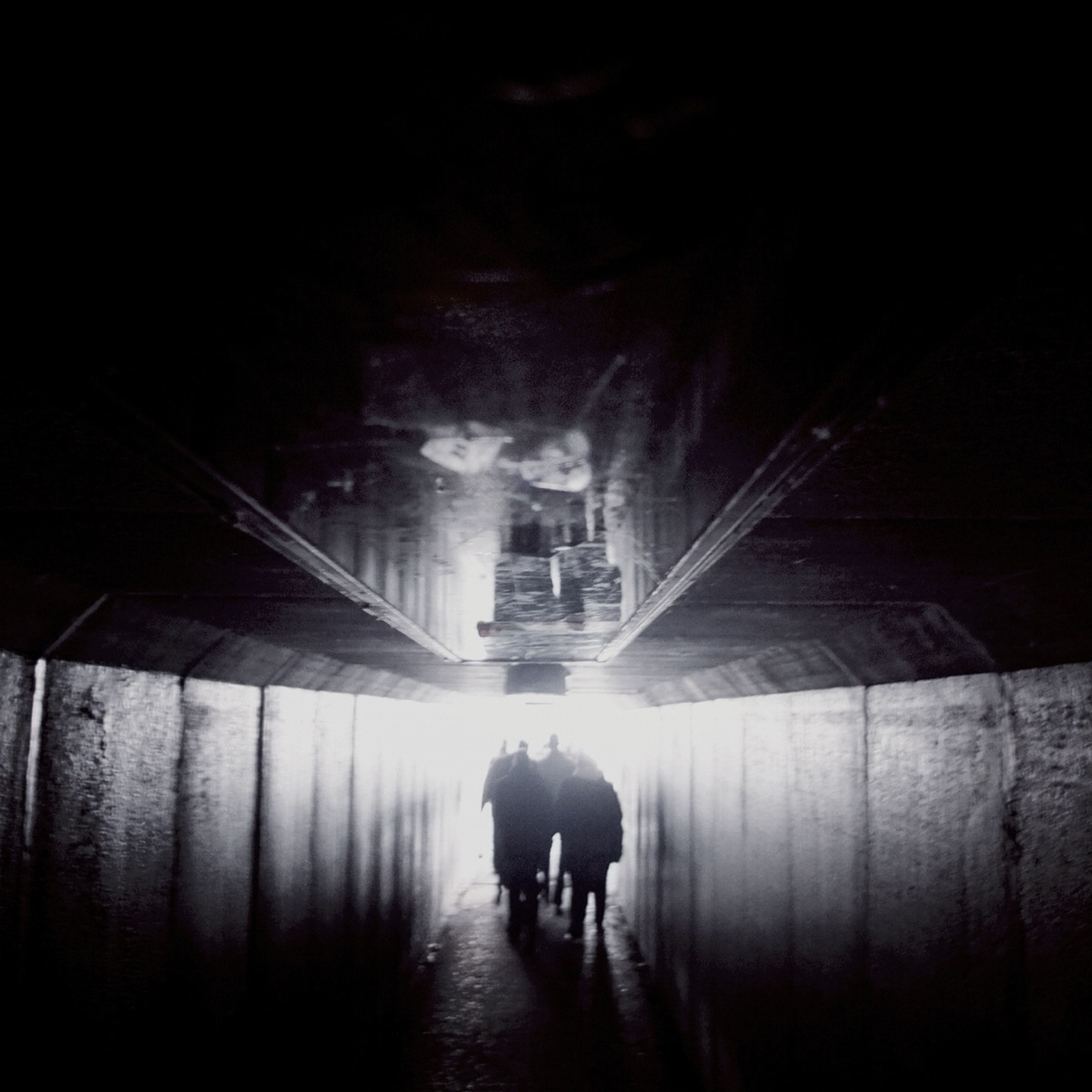 walking, architecture, rear view, men, lifestyles, full length, the way forward, built structure, indoors, tunnel, leisure activity, person, illuminated, building exterior, diminishing perspective, night
