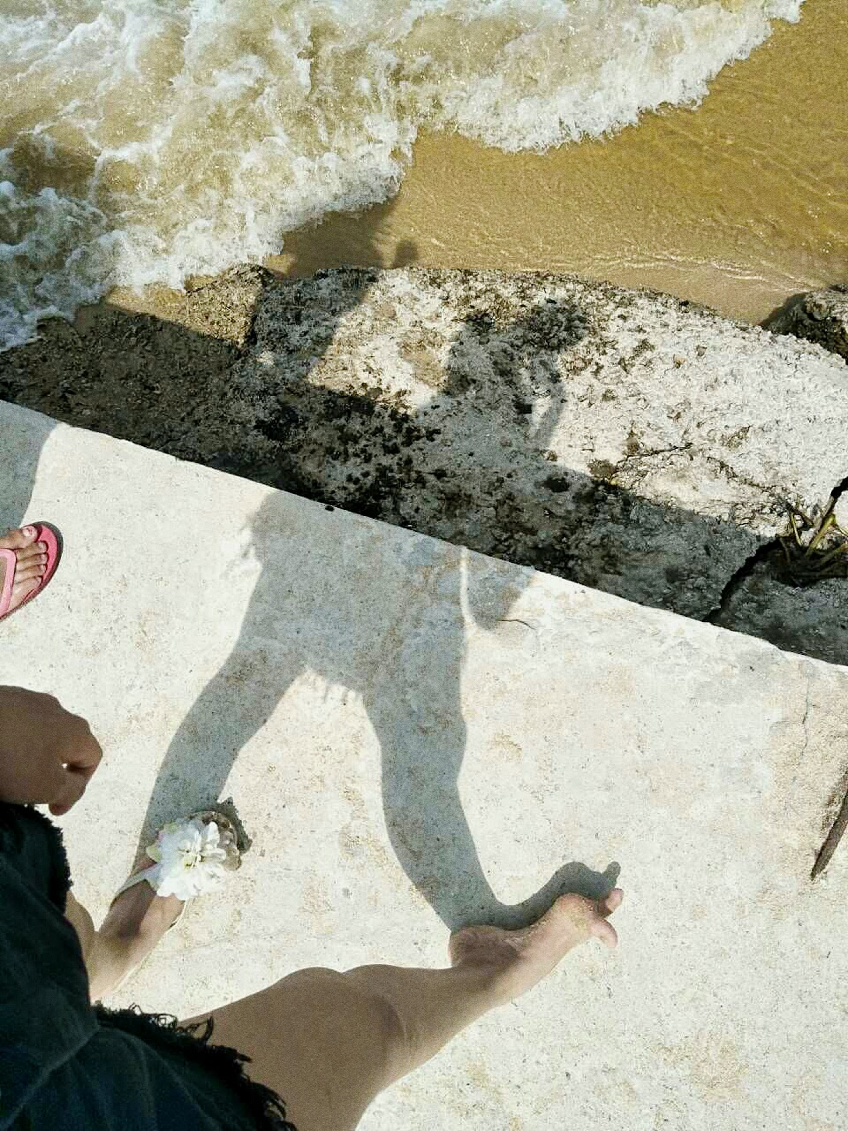 shadow, sunlight, day, real people, high angle view, outdoors, human body part, one person, low section, human hand, water, nature, one man only, only men, people