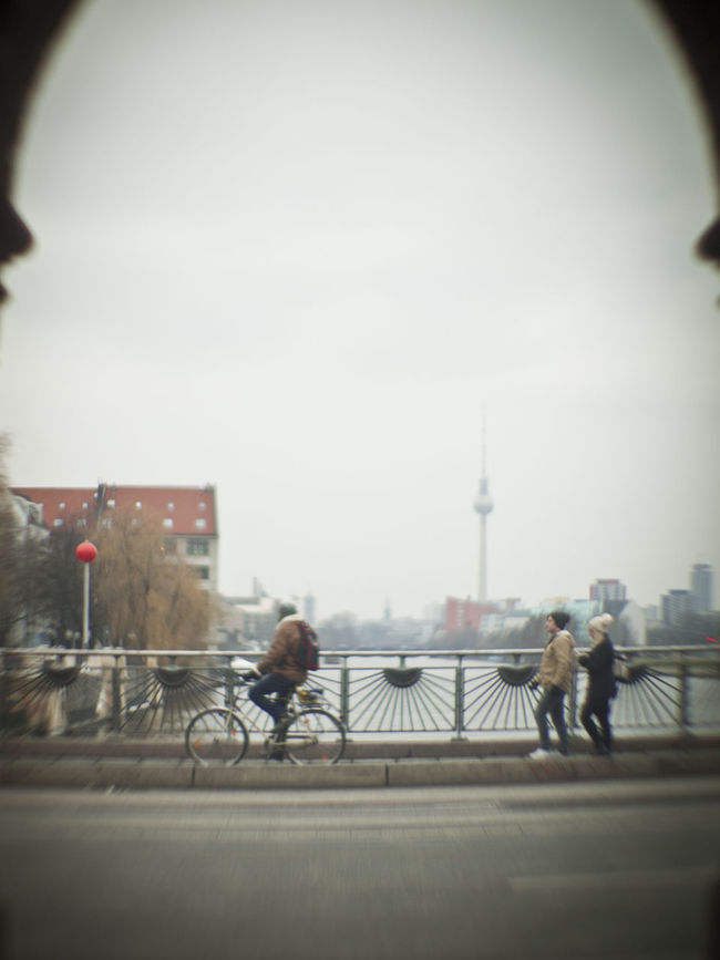 Architecture Bicycle Blurred Motion Bridge - Man Made Structure Built Structure Casual Clothing City City Life Cycling Day Leisure Activity Lifestyles Men Person Railing Road Sky Street Tourism Transportation Travel Destinations Urban Skyline Walking