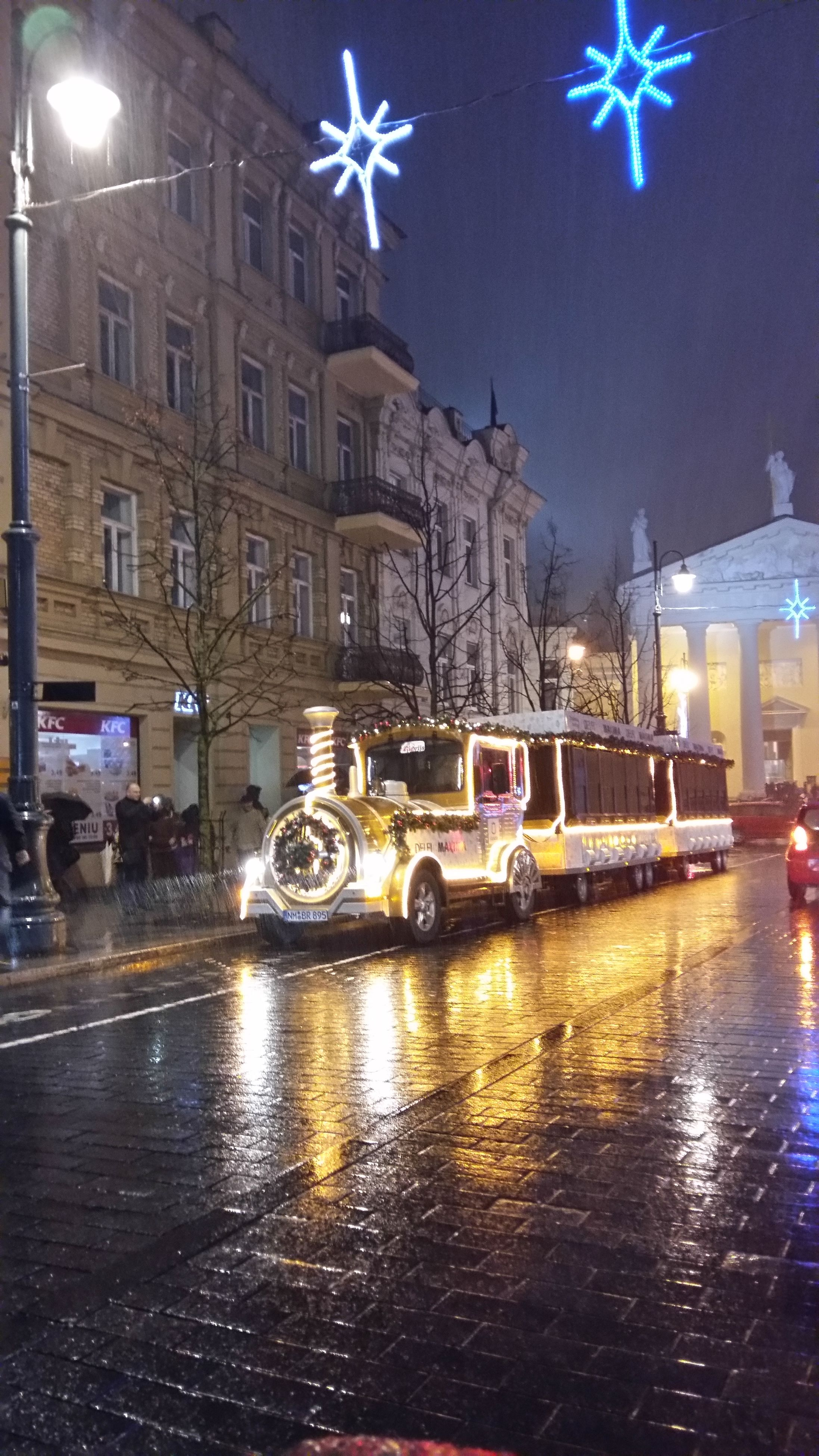 night, illuminated, reflection, winter, city, building exterior, street, snow, architecture, christmas, snowing, city street, cold temperature, built structure, transportation, car, water, christmas decoration, mode of transport, city life, puddle, outdoors, no people, christmas tree