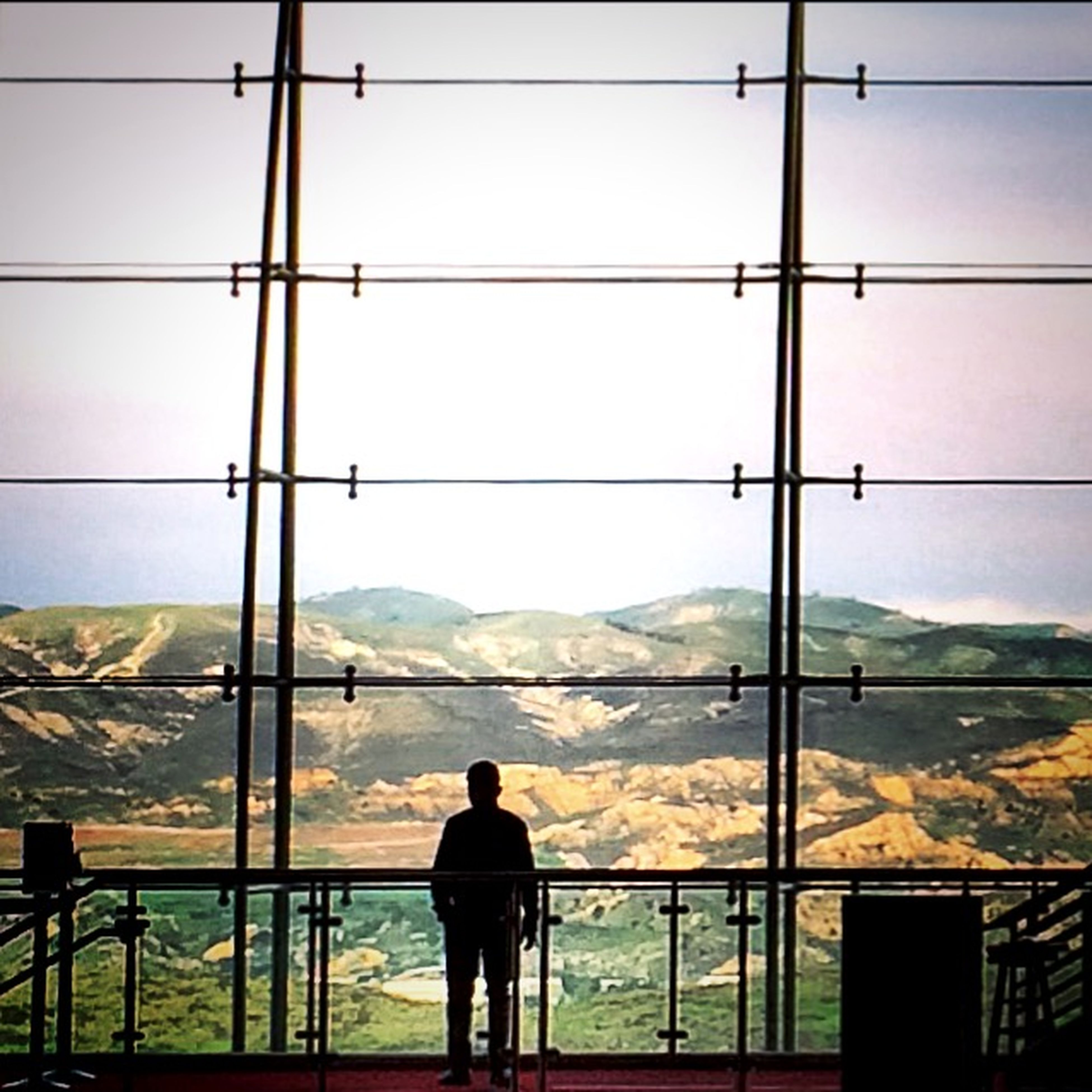 standing, rear view, lifestyles, men, mountain, leisure activity, full length, railing, sky, looking at view, person, three quarter length, silhouette, water, indoors, nature, day, tranquility