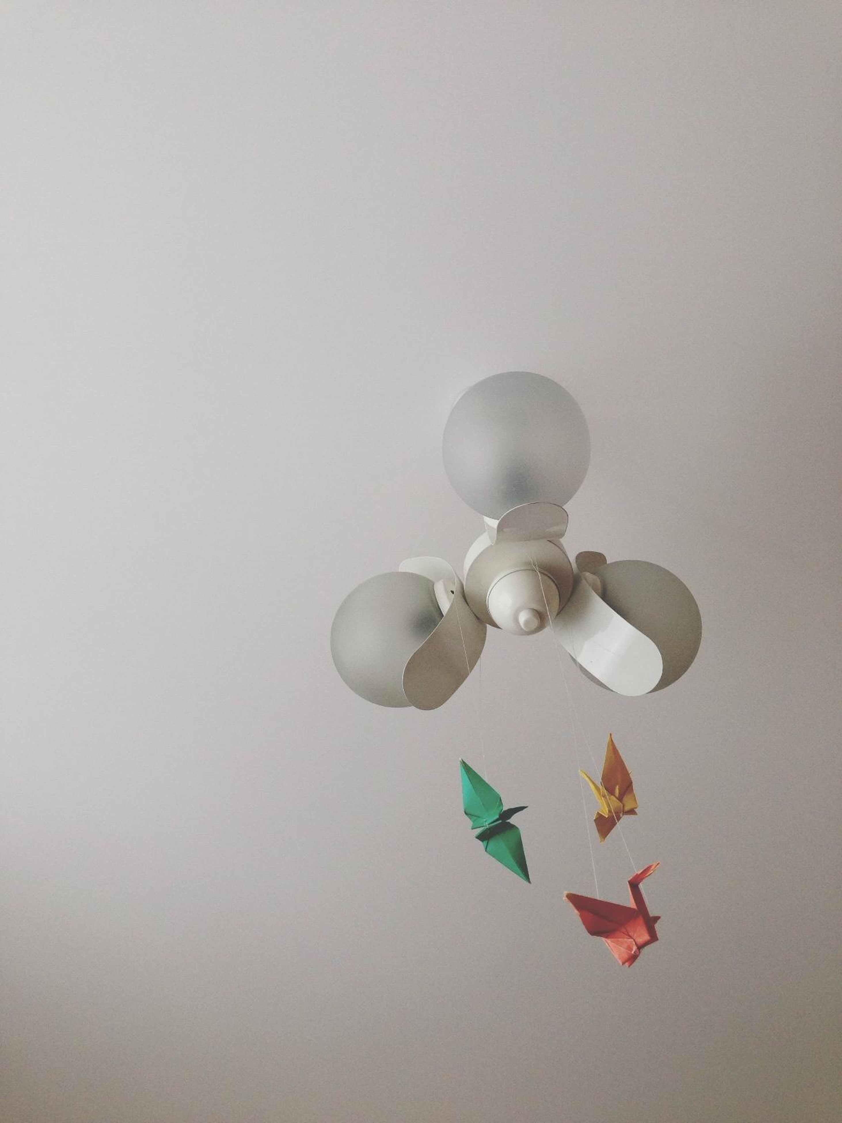 indoors, still life, copy space, creativity, hanging, decoration, art and craft, art, low angle view, lighting equipment, ceiling, studio shot, wall - building feature, no people, single object, white color, close-up, ideas, multi colored, electric lamp