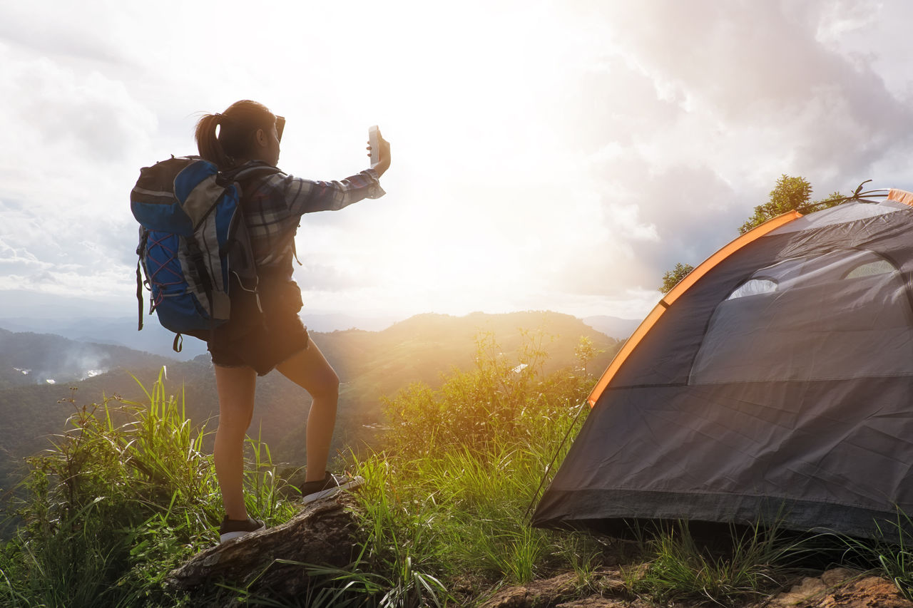 Woman By Tent On Mountain Taking Selfie From Mobile Phone Against Sky