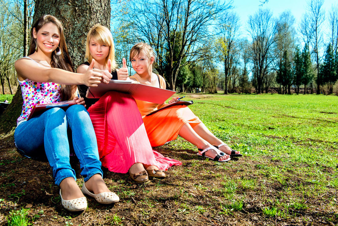 Students with thumbs up outdoors Bright Colors Friends Happy Students Summertime Trees Cheerful Day Friendship Full Length Girls Grass Outdoors Park - Man Made Space People Spring Springtime Styding Summer Sunny Day Teenage Girls Teenager Thumbs Up Togetherness Young Adult