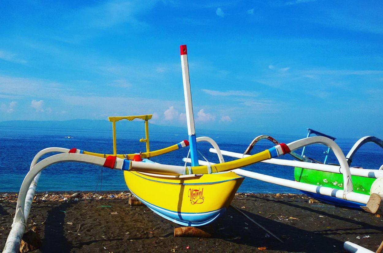 Jukung is a traditional wooden boat. Jukung Colorfull Traditionalboat Bluesky Blubeach Blacksand Pengalonbeach Karangasem Bali INDONESIA