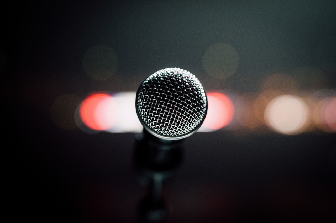 microphone, focus on foreground, single object, close-up, music, no people, indoors, microphone stand, sound recording equipment, technology, arts culture and entertainment, illuminated, night, defocused