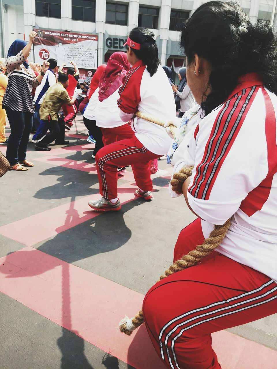 real people, cultures, traditional clothing, performance, traditional festival, medium group of people, street, men, tradition, day, women, outdoors, performing arts event, red, skill, traditional dancing, musician, city, adult, people