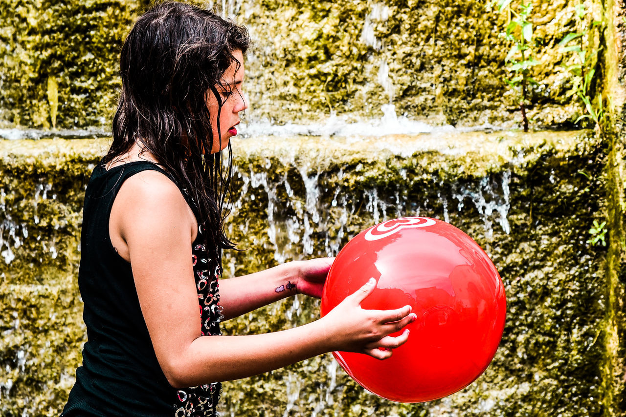 red, playing, one person, balloon, real people, ball, side view, casual clothing, outdoors, holding, lifestyles, leisure activity, standing, day, young adult, young women, tree, nature, adult, people