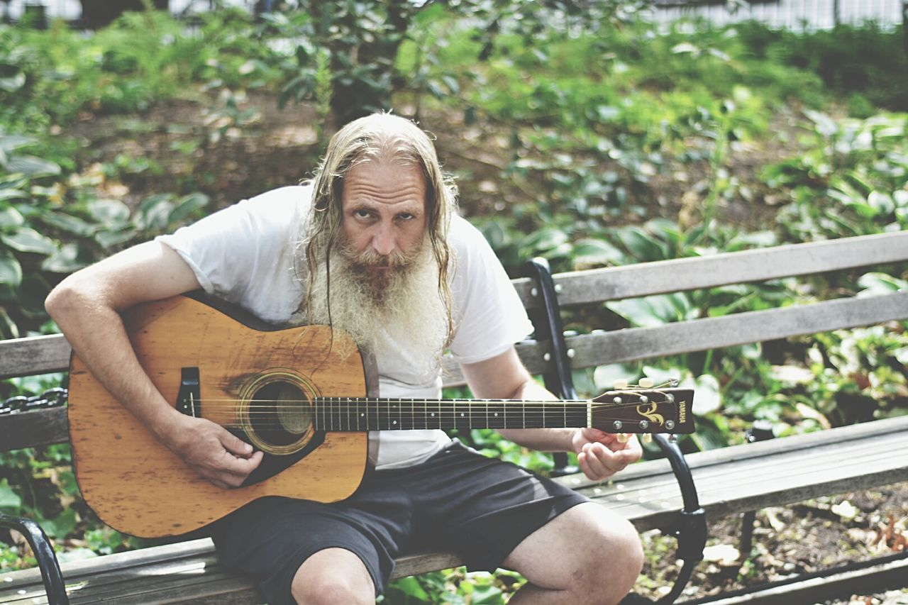 guitar, sitting, casual clothing, one person, playing, leisure activity, three quarter length, day, outdoors, real people, music, musical instrument, front view, lifestyles, plucking an instrument, beard, young adult, musician, people