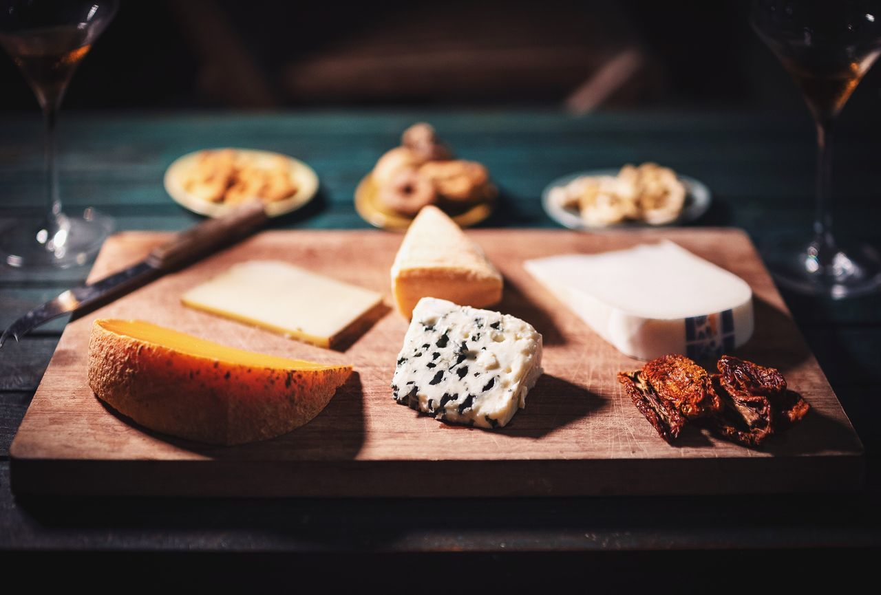 Close-Up Of Cheese Slices On Chopping Board