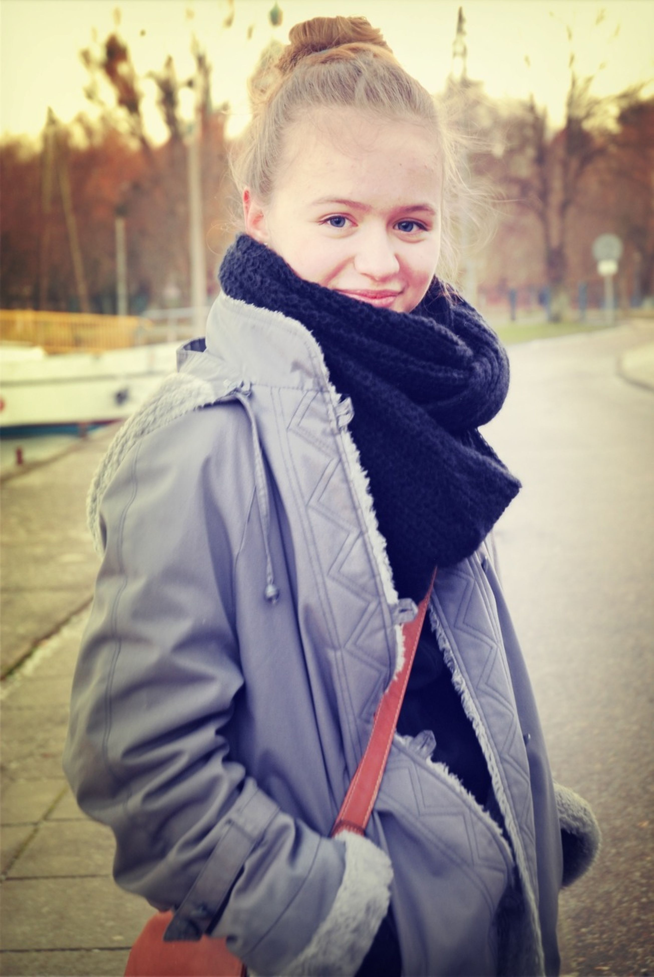 casual clothing, lifestyles, focus on foreground, leisure activity, warm clothing, person, jacket, front view, street, transportation, car, waist up, young adult, standing, looking at camera, sitting, three quarter length, incidental people