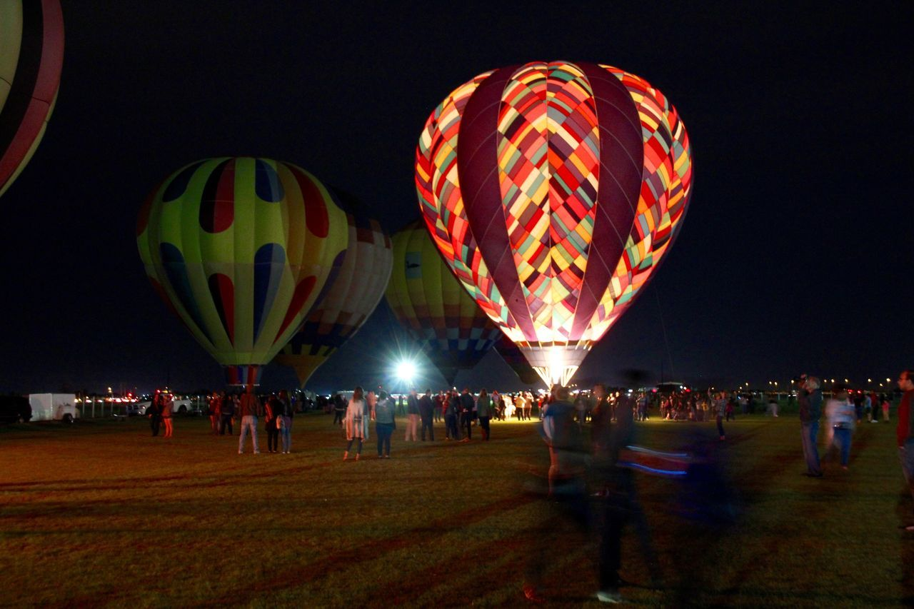 large group of people, leisure activity, illuminated, night, real people, multi colored, arts culture and entertainment, celebration, lifestyles, women, outdoors, adventure, men, ballooning festival, crowd, sky, hot air balloon, people