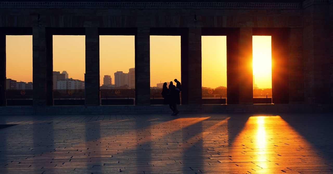 sunset, architecture, real people, built structure, silhouette, lifestyles, men, sunlight, building exterior, women, architectural column, leisure activity, two people, city, standing, full length, sky, indoors, urban skyline, day, adult, people