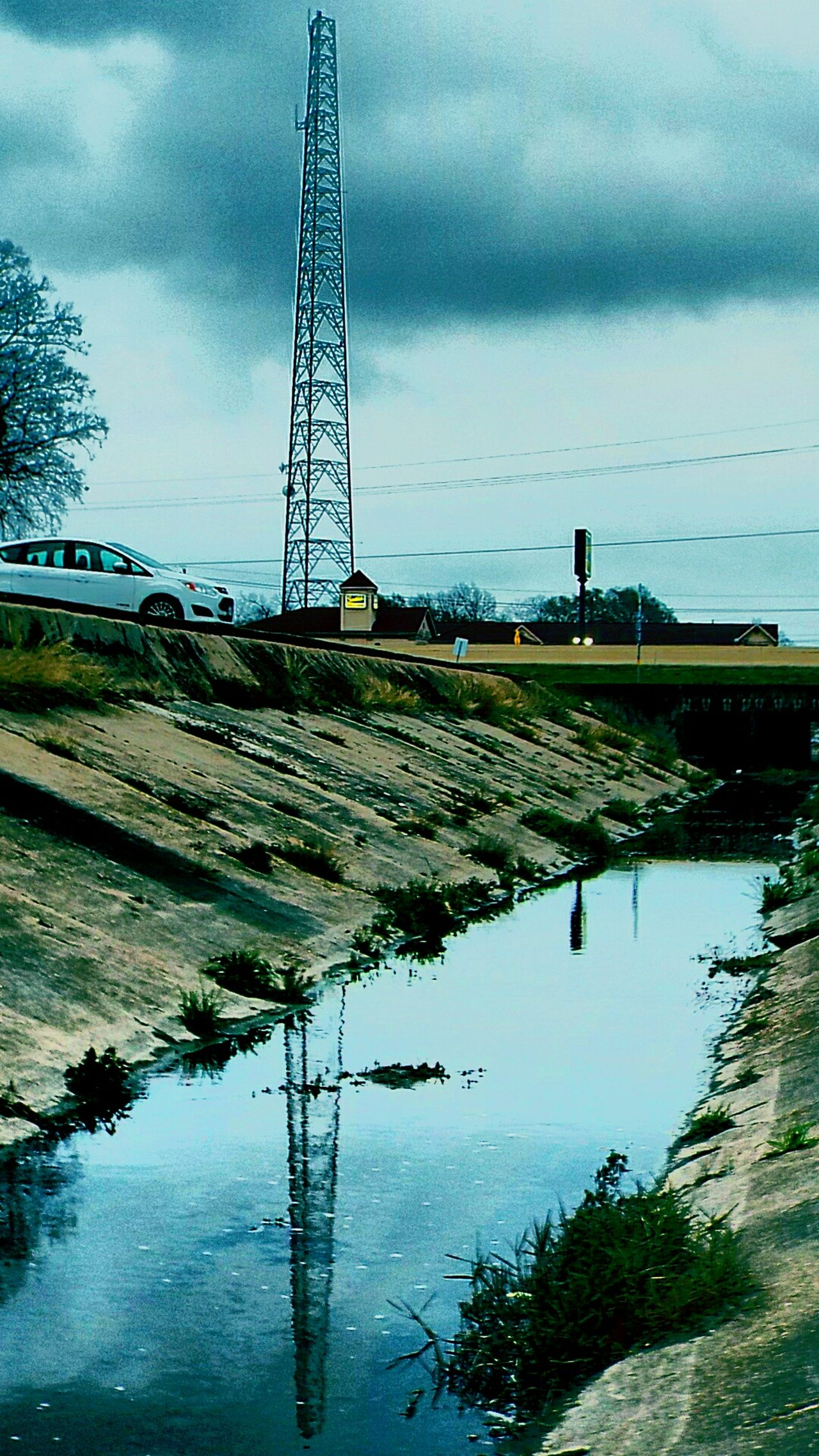 On The Bayou Drainageditch Reflection Of Satellite Tower In The Ditchwater Dusk Gloomy Days
