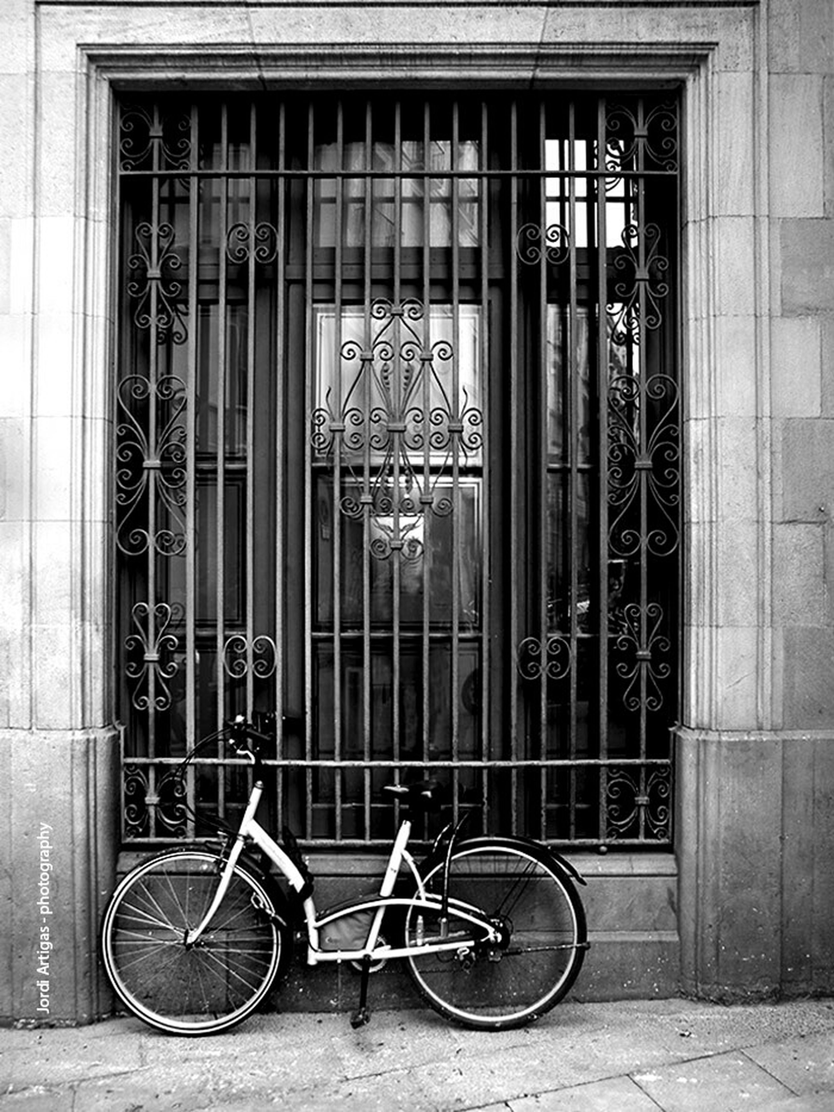 architecture, building exterior, built structure, bicycle, window, stationary, mode of transport, closed, building, door, parked, transportation, land vehicle, city, metal, parking, wall - building feature, gate, brick wall, day