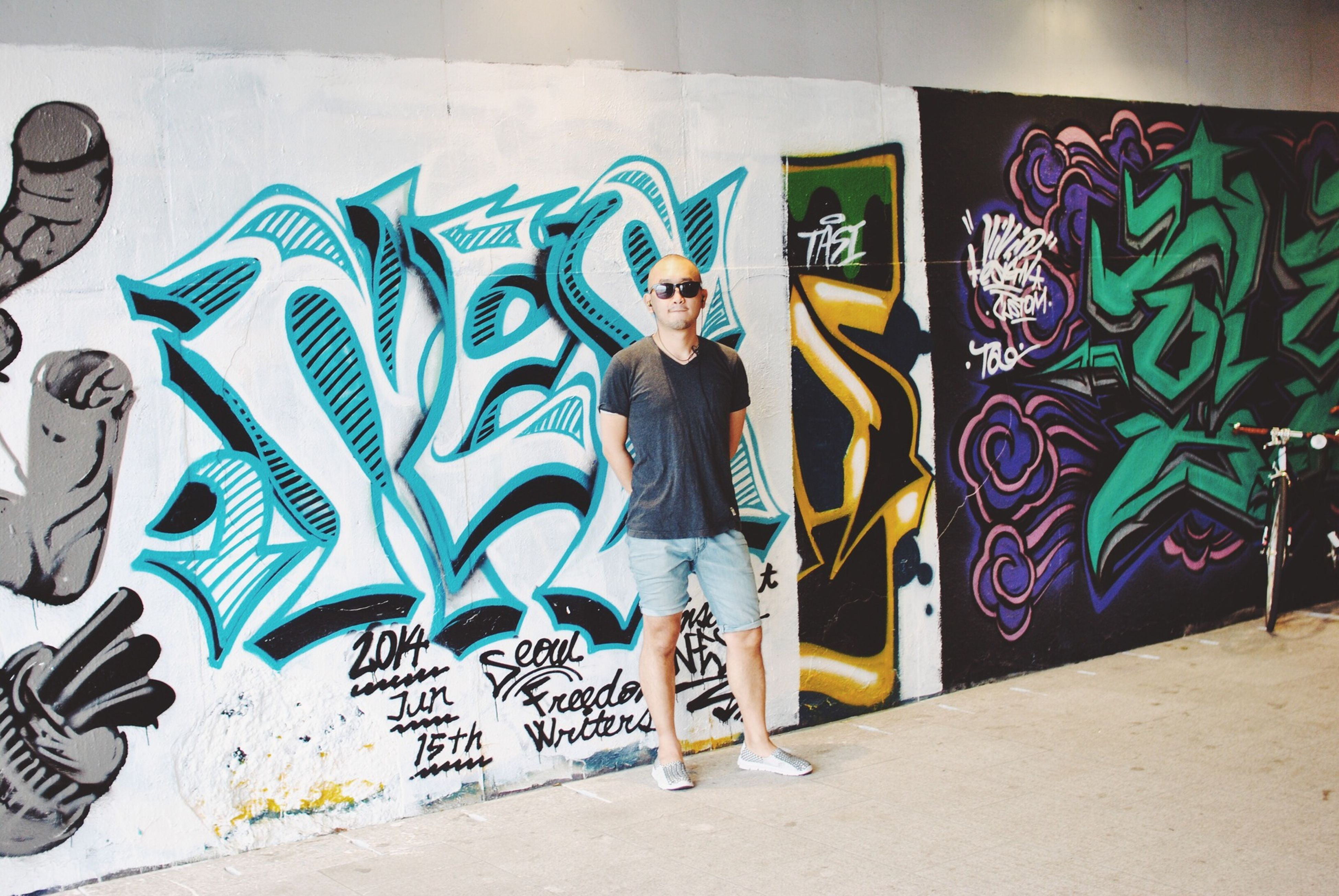 graffiti, lifestyles, wall - building feature, creativity, art, art and craft, standing, casual clothing, leisure activity, multi colored, built structure, architecture, young adult, day, full length, indoors, young women, wall