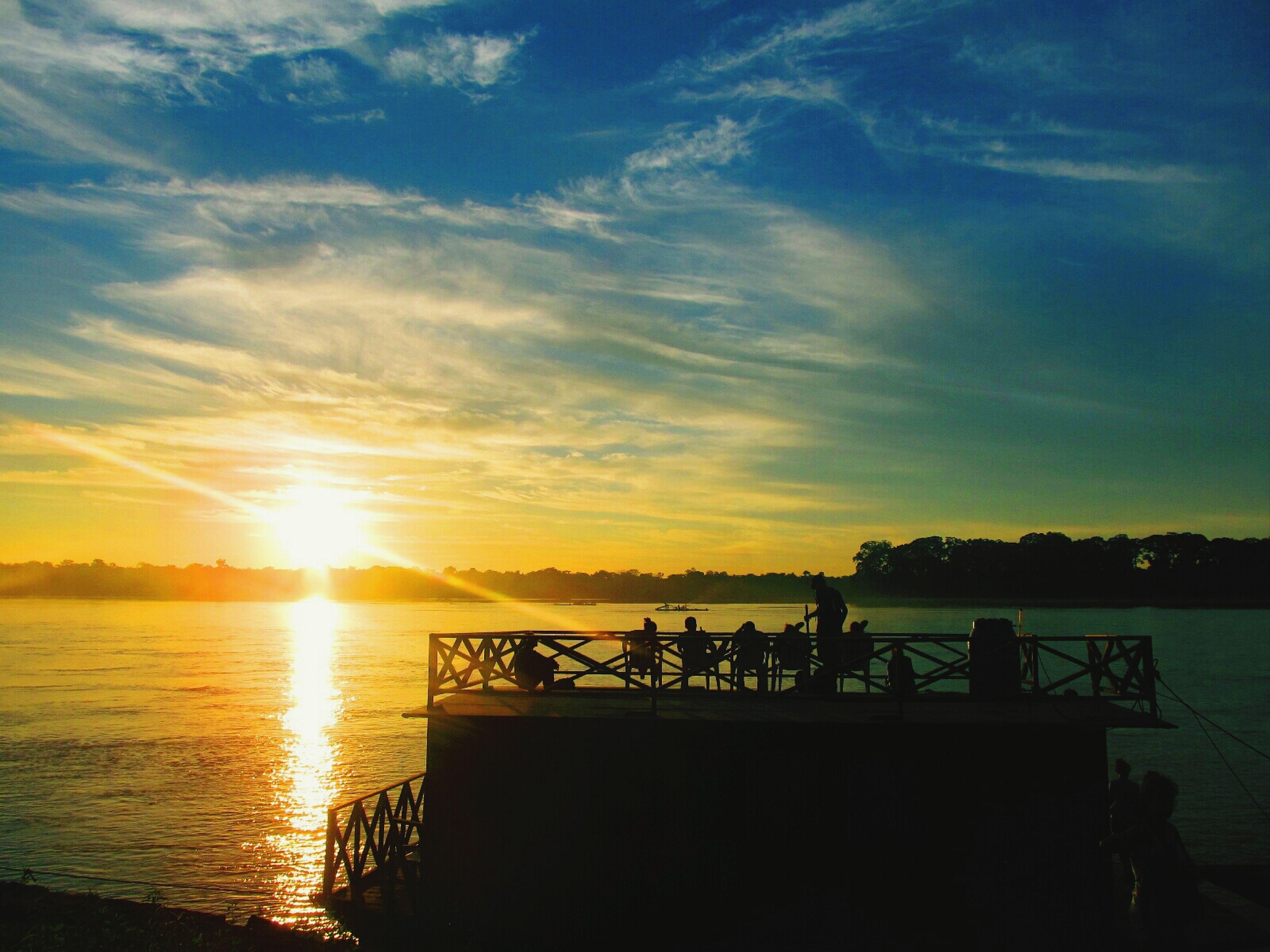 sunset, silhouette, water, sun, scenics, tranquil scene, sky, beauty in nature, tranquility, orange color, sea, nature, reflection, idyllic, sunlight, cloud - sky, horizon over water, sunbeam, men