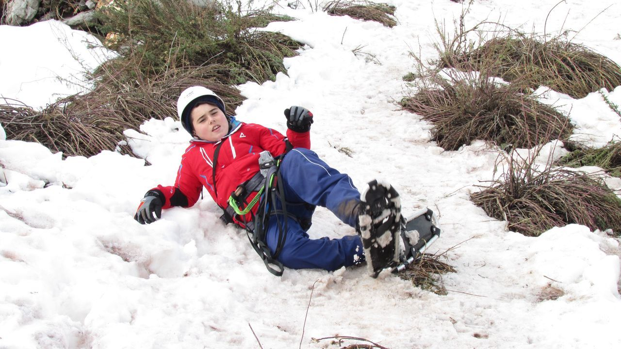 Boy Lying In Snow Covered Field By Bushes