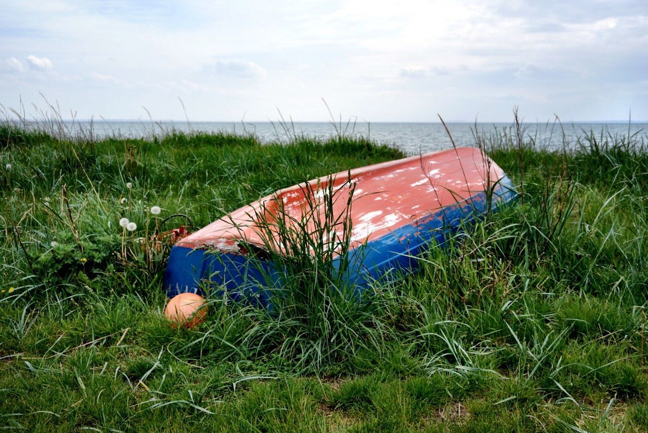 Boat Moored On Grassy Field Against Sea