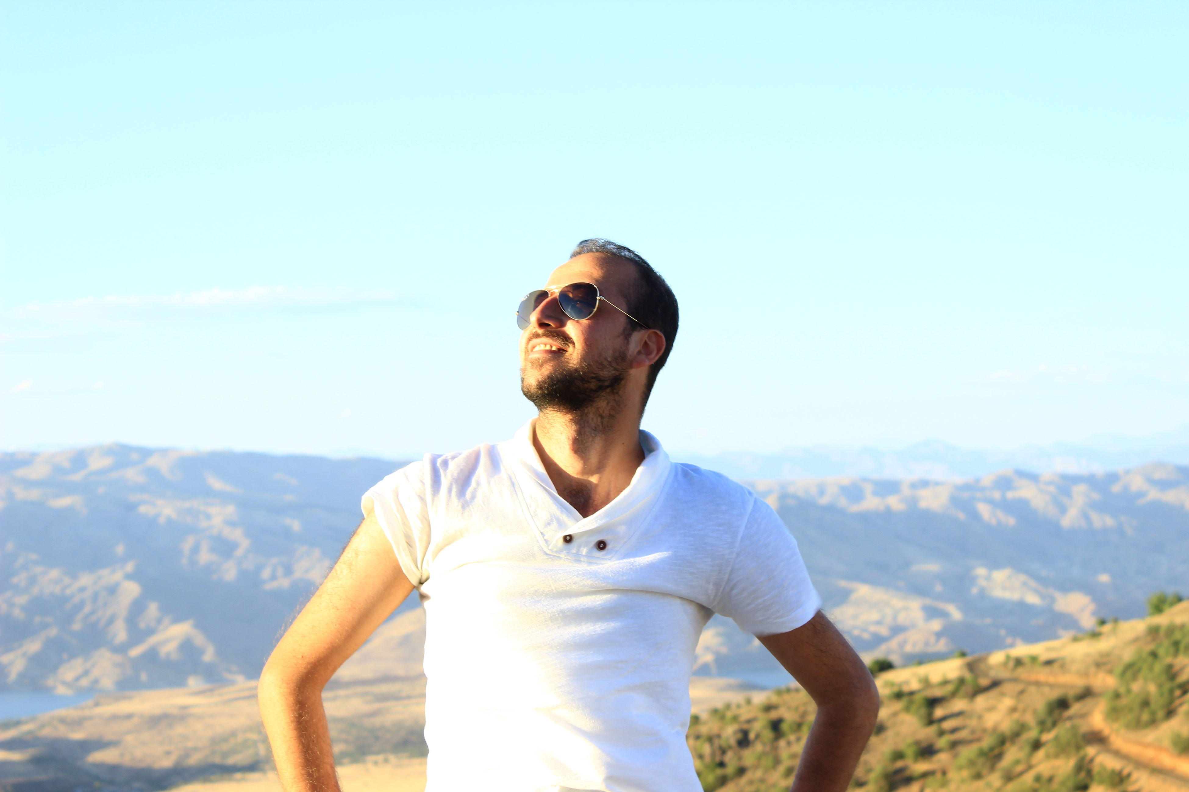 lifestyles, young men, leisure activity, young adult, mountain, sunglasses, person, looking at camera, portrait, sky, casual clothing, photography themes, front view, holding, clear sky, photographing, mid adult men, mountain range