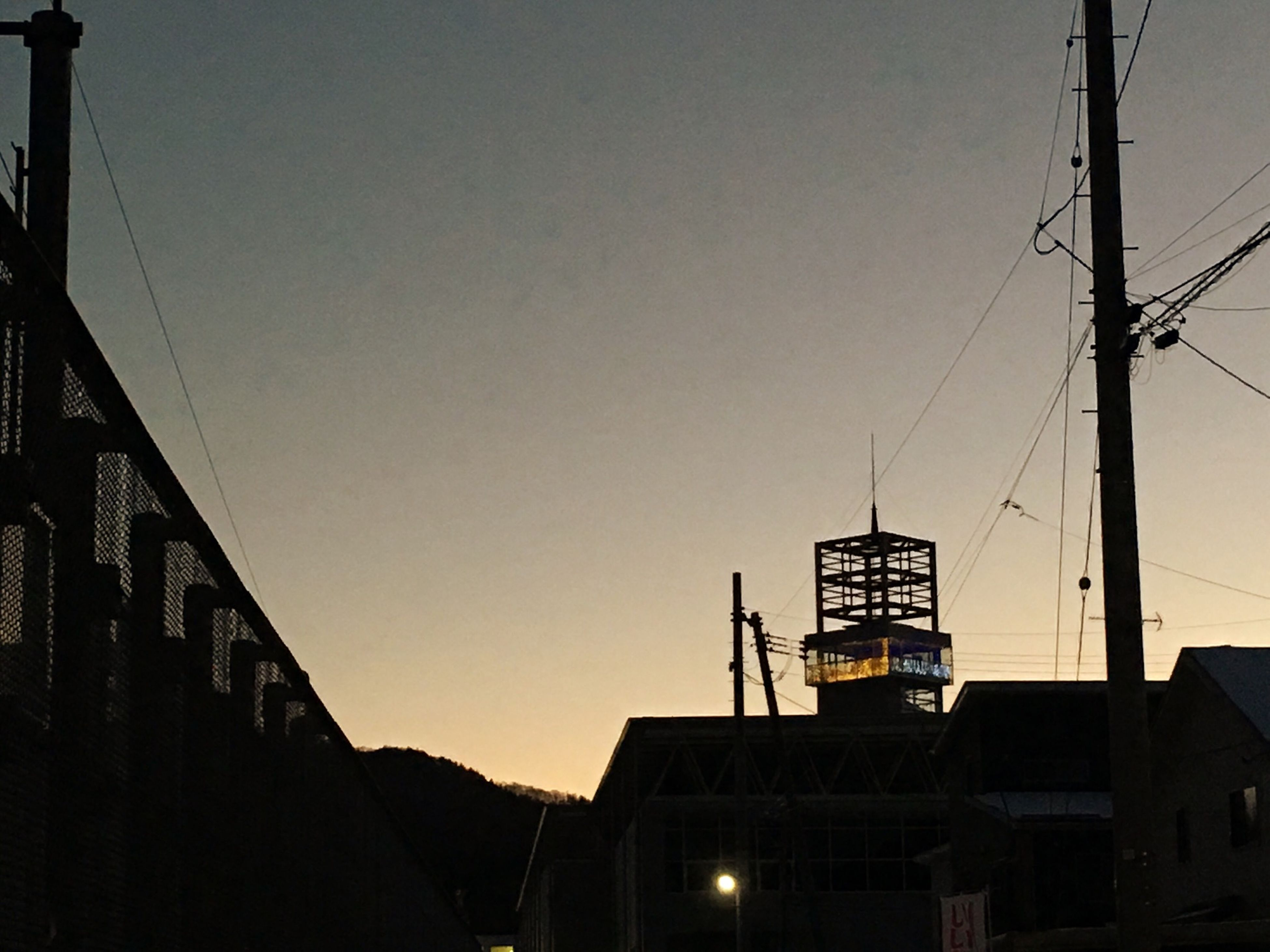 architecture, built structure, building exterior, clear sky, low angle view, copy space, silhouette, building, residential building, power line, street light, construction site, sunset, dusk, outdoors, city, sky, residential structure, cable, crane - construction machinery
