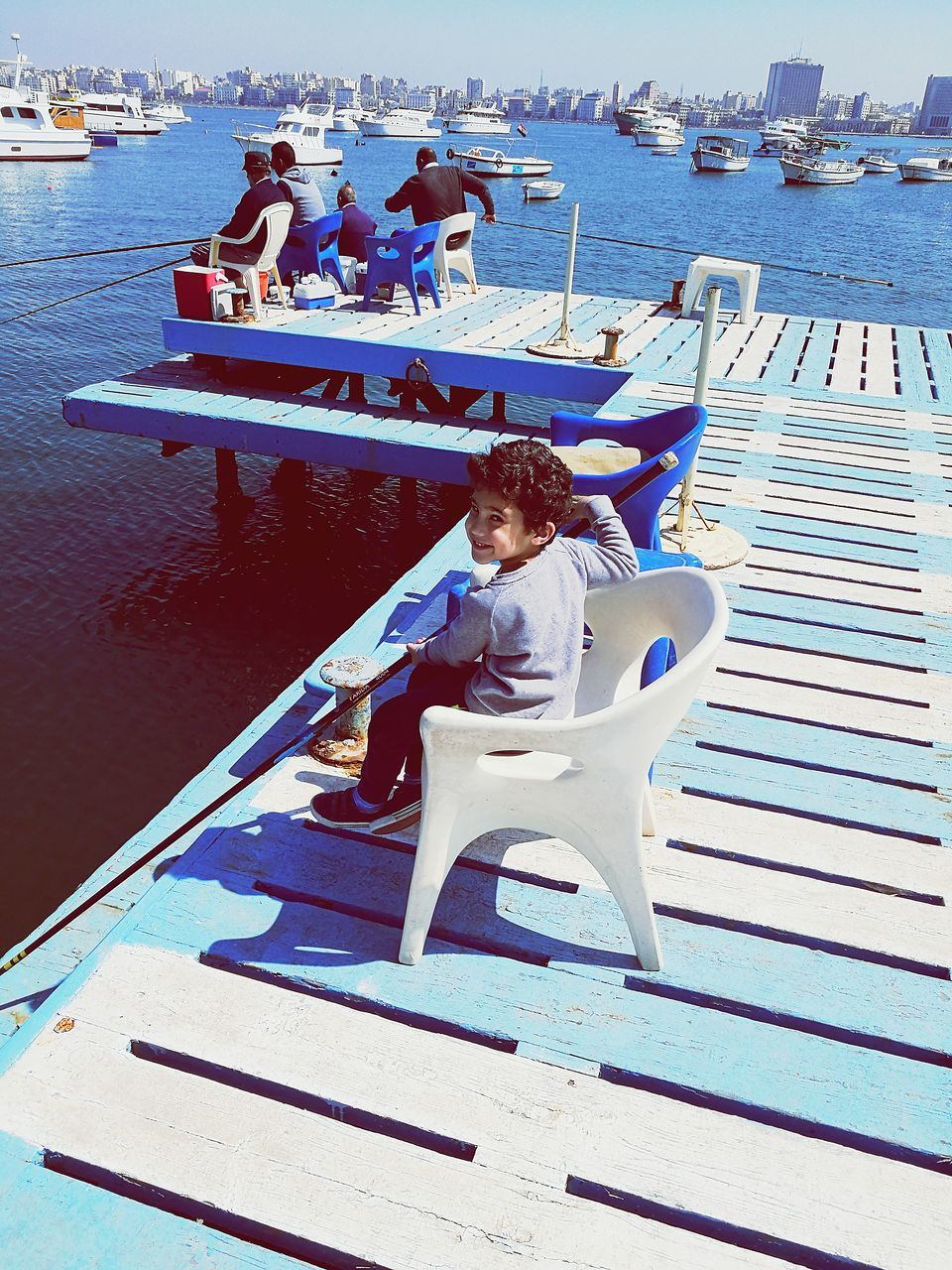 nautical vessel, transportation, sitting, full length, sea, boat, mode of transport, water, real people, one person, moored, day, outdoors, casual clothing, leisure activity, yacht, beach, women, sailboat, sailing, vacations, lifestyles, harbor, young adult, men, sailor, nature, sky, adult, people