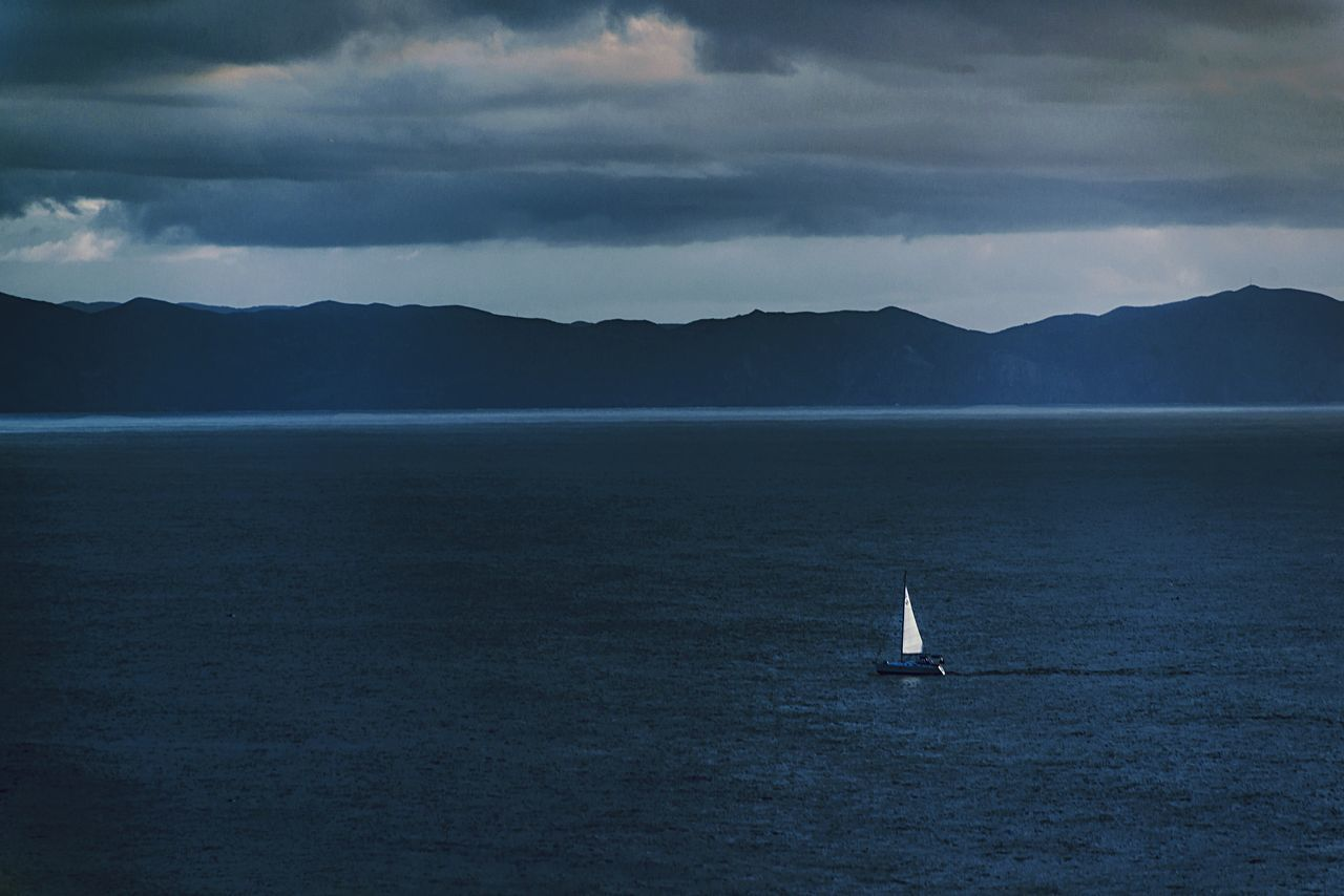 The Lone Boat Sea Nautical Vessel Mountain Water Sailing Transportation Sky Cloud - Sky Sailboat No People Waterfront Nature Ocean Beach Beauty In Nature Outdoors Scenics Tranquility Day Yacht Yachting