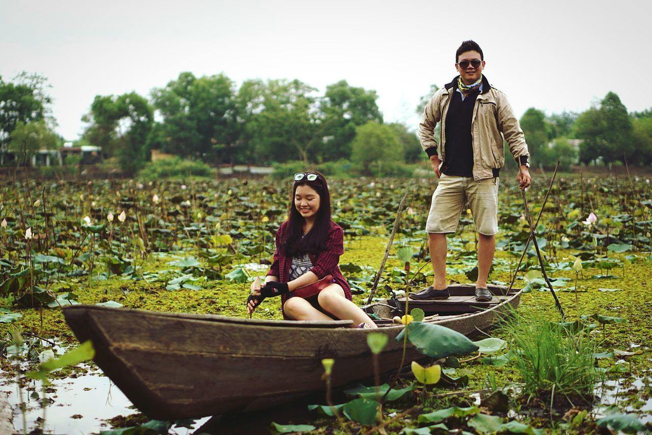 two people, real people, young women, young adult, full length, togetherness, field, day, leisure activity, mid adult men, lifestyles, front view, looking at camera, young men, casual clothing, outdoors, nature, growth, standing, sitting, portrait, smiling, beautiful woman, sky, adult, people