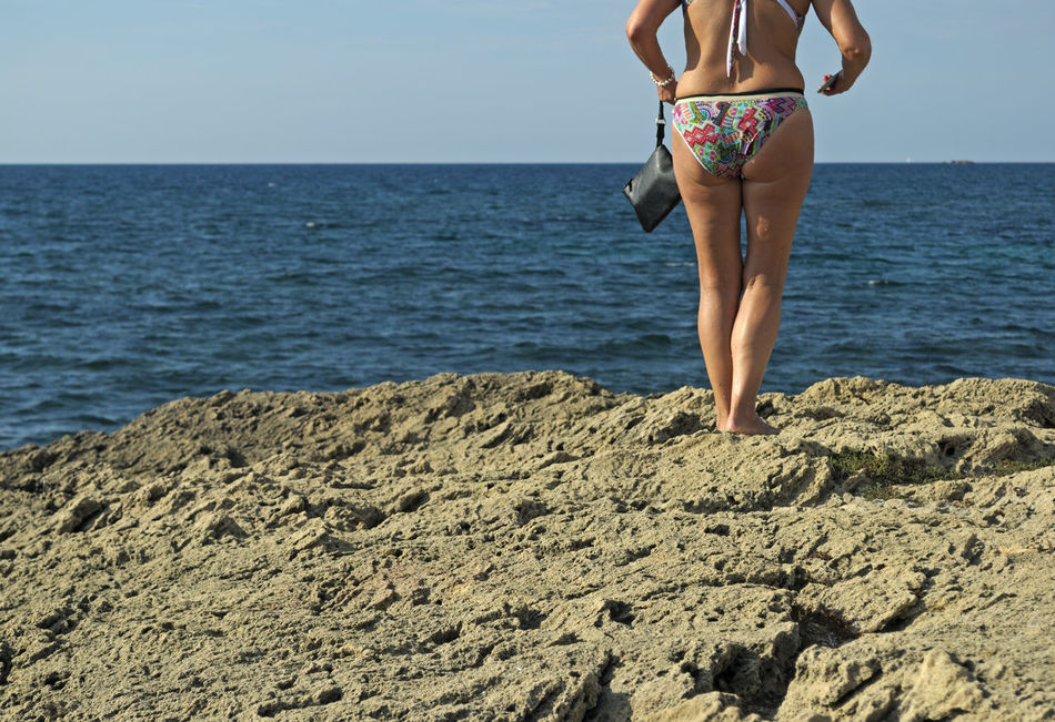 woman standing looking out to sea in Sardinia, Italy Back View Bather Beach Coast Horizon Over Water Leisure Activity Low Section One Woman Only People Person Rear View Rocky Beach Sea Seashore Summer Swimsuit Swimwear Unrecognizable Vacations Woman